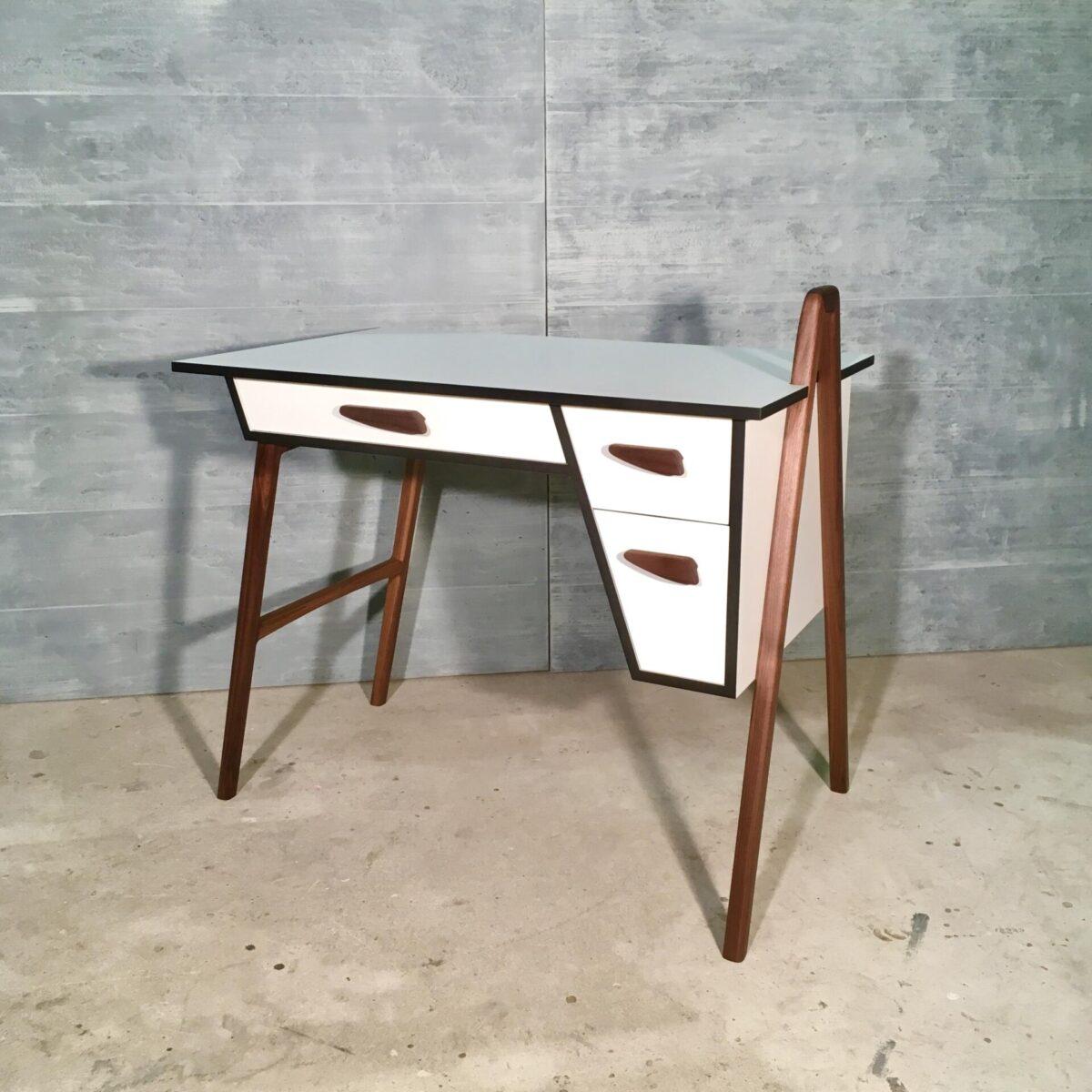 Schreibtisch mit Schubladen 96cm mal 60cm. Weisse Cdf Platte mit schwarzem Kern, kombiniert mit Nussbaum Vollholz. Dieser Tisch ist eine Einzelanfertigung von uns, von Grund auf geplant, das Design ausgearbeitet und ausgeführt. Die Cdf Platte ist eine robuste kratzfeste Oberfläche. Die drei Schubladen, mit den grösstenteils von Hand geschnitzten griffen, bieten Platz für die nötigen Schreibtisch Utensilien. Die Tischbeine rechts sind oberhalb der Tisch Oberfläche verbunden. Dort lässt sich ein Buch anlehnen oder ein klemm Spot montieren. Der Tisch kann im auch frei im Raum gestellt sein da die Rückseite sauber verarbeitet ist. Zusätzlich bietet sich ein kleines Fach um ein Dekorations Gegenstand auszustellen.