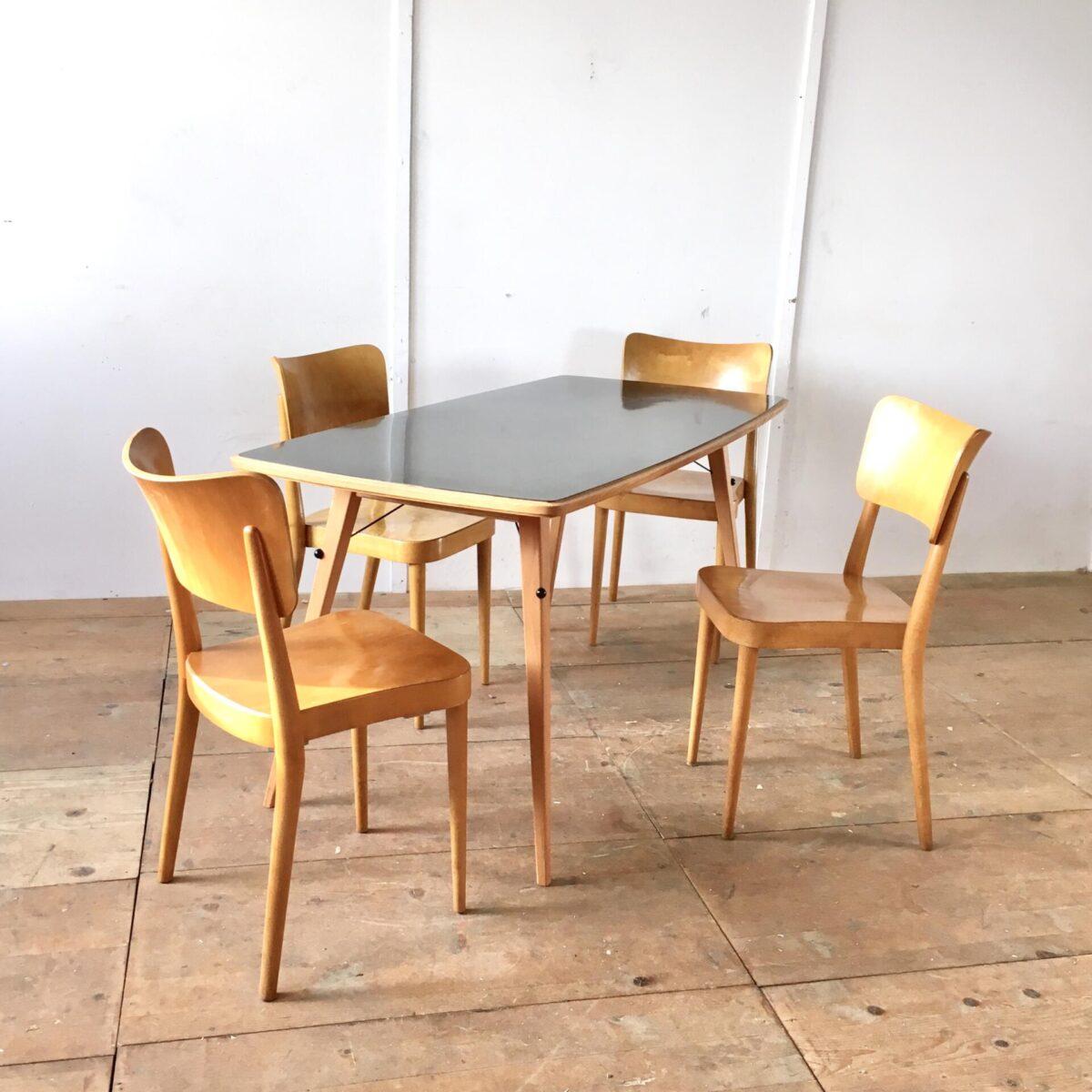 Vintage Küchentisch 160cm mal 75cm. Schwarze Kelko Oberfläche mit Eschenholz Umrandung. Dieses Tischblatt ist ohne Tischgestell zu uns gekommen. Wir haben ein Buchenholz unterbau, passend zu der Zeit, geschreinert. Das schwarze Kunststoff Element der Tischplatte haben wir unten nochmal aufgegriffen. In Form von schwarzen Metall Verstrebungen die von Kunststoff Kugeln gehalten werden.