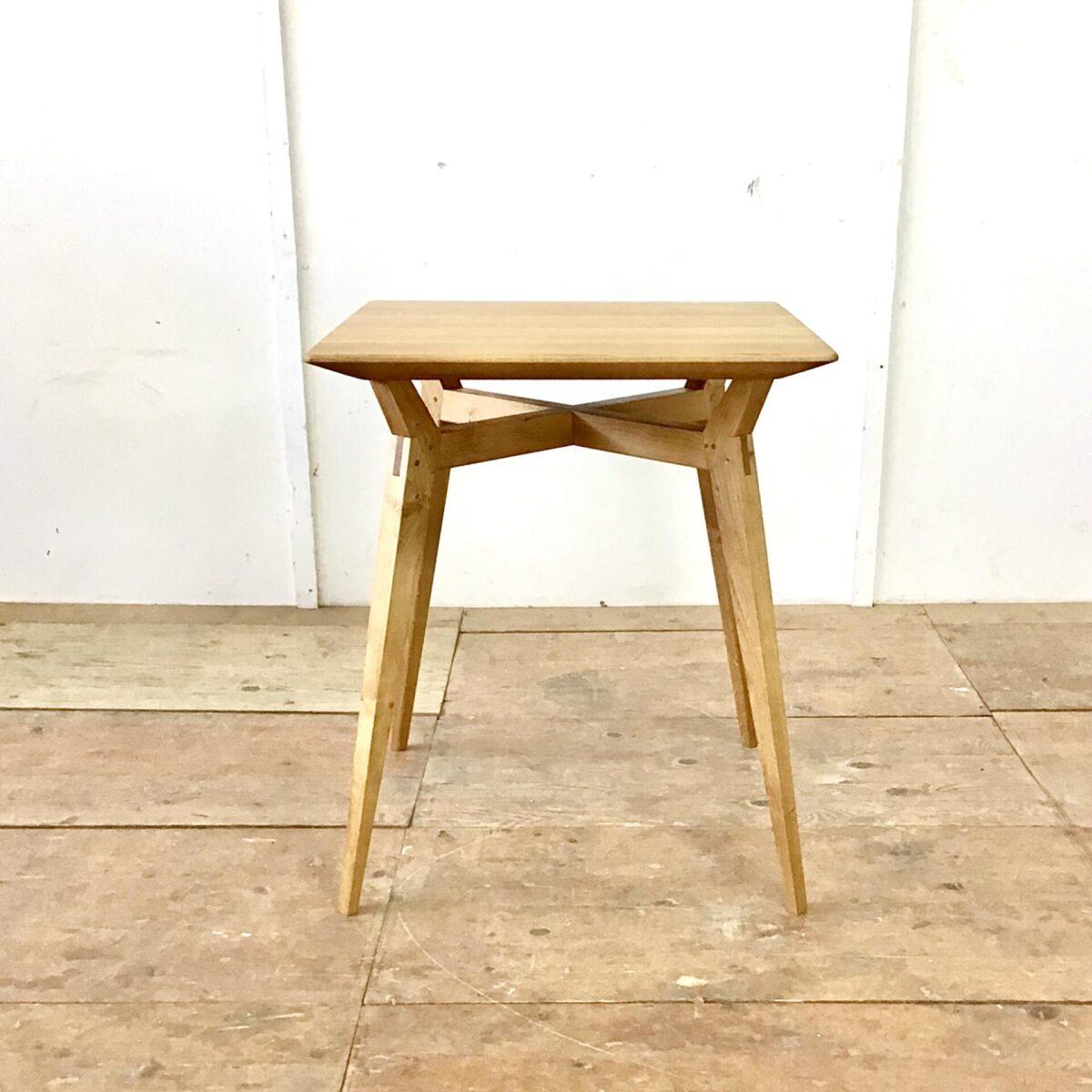 Deuxieme.shop Kleiner Pausen Tisch 66 mal 66cm Höhe 75cm. Eiche Massivholz mit Insekten artigen Tischgestell. Kreuzzargen überblattet, freiliegend unter dem Tischblatt. Tischbeine und Zargen sind mit Schlitz und Zapfen verbunden. Zusätzlich mit Messing Stiften verzapft. Dieser Tisch ist aus Eichen Holz entstanden das nicht länger war als 66cm. Die aufwändigen Holzverbindungen sind grösstenteils von handgefertigt. Der Tisch ist mit Naturöl behandelt.