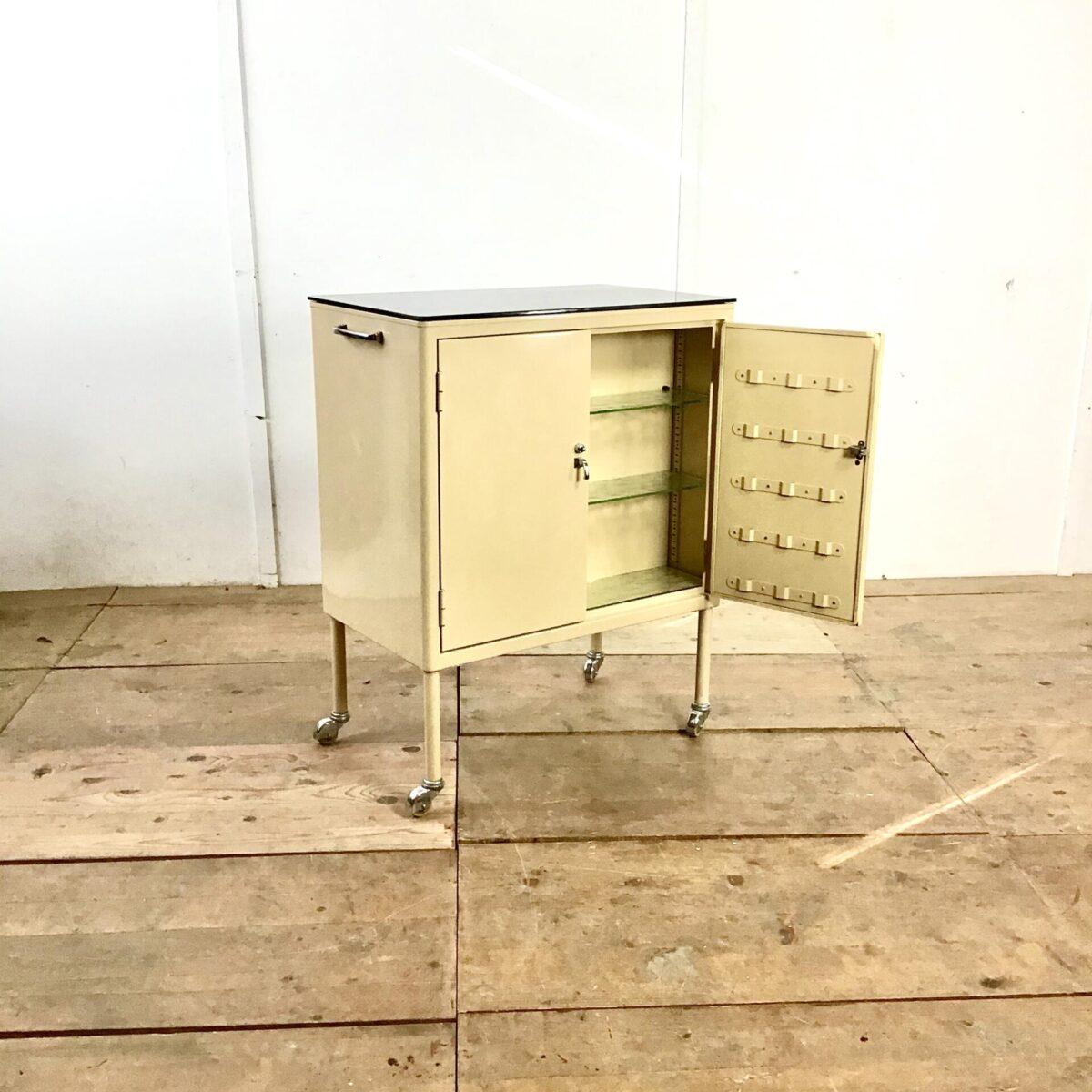 Metall Möbel 76cm mal 46cm Höhe 95.5cm. Rollkorpus Creme braun lackiert mit verchromten Griffen und Profilen. Das Möbel hat auf beiden Seiten Stau Raum. Die Oberfläche ist geschwärztes Glas. Die Möbel Rollen laufen gut, mit den seitlichen Griffen lässt es sich einwandfrei bewegen. Praktisch als Beistelltisch oder Schnapswagen.