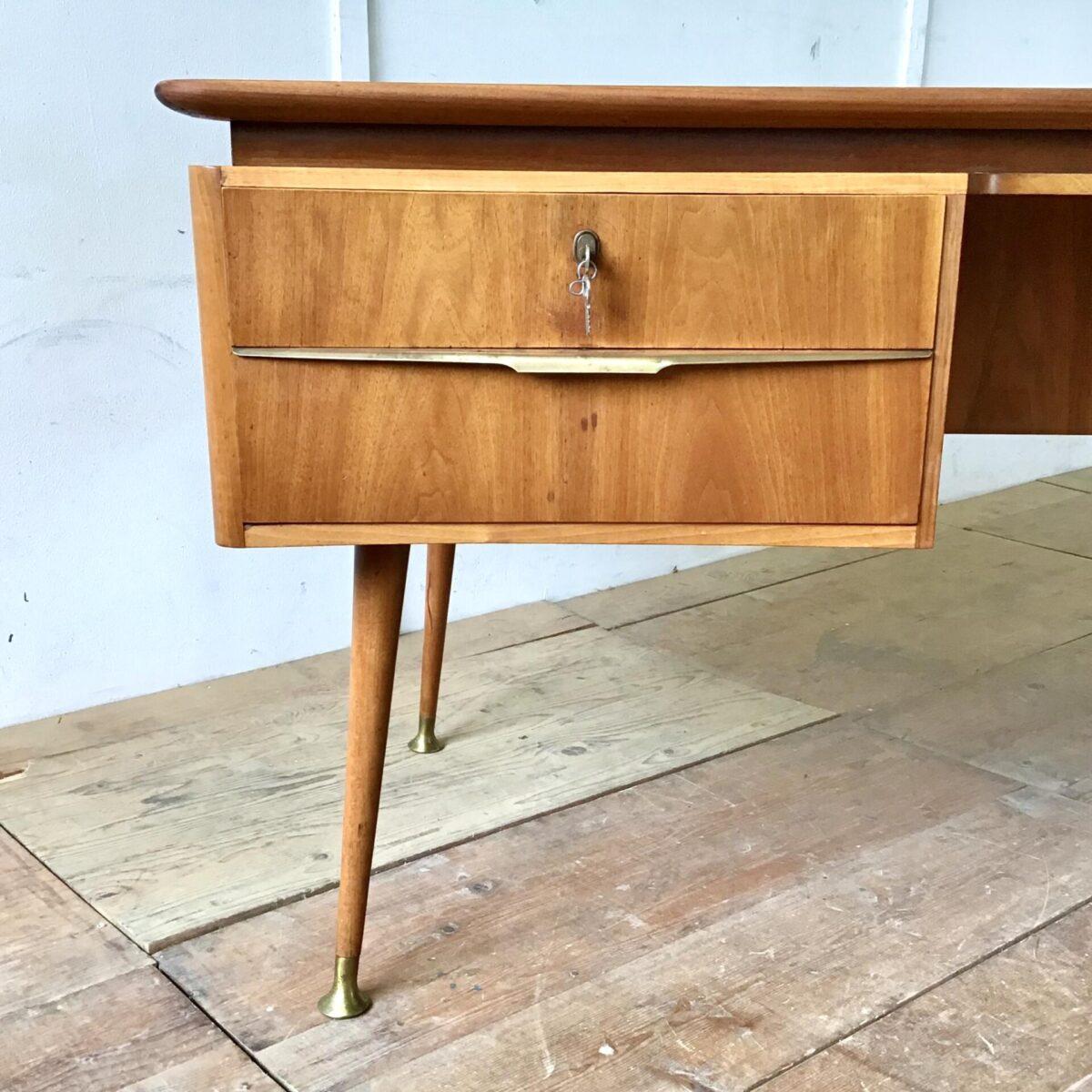 Vintage Schreibtisch 60er Jahre 174cm mal 78cm Höhe 76cm Beinfreiheit breite 60cm. Der Tisch ist aus Nussbaum furniert. Schubladen Griffe Messing leicht patiniert. Die konisch runden Füsse sind aus Buchenholz, mit schönen Messing Standfüssen. Die Grundform des Tisches ist leicht gebogen. Auch die Rückseite ist schön verarbeitet mit dem länglichen Fach und dem Auszug Tablar. Ideal um frei im Raum zu stehen.