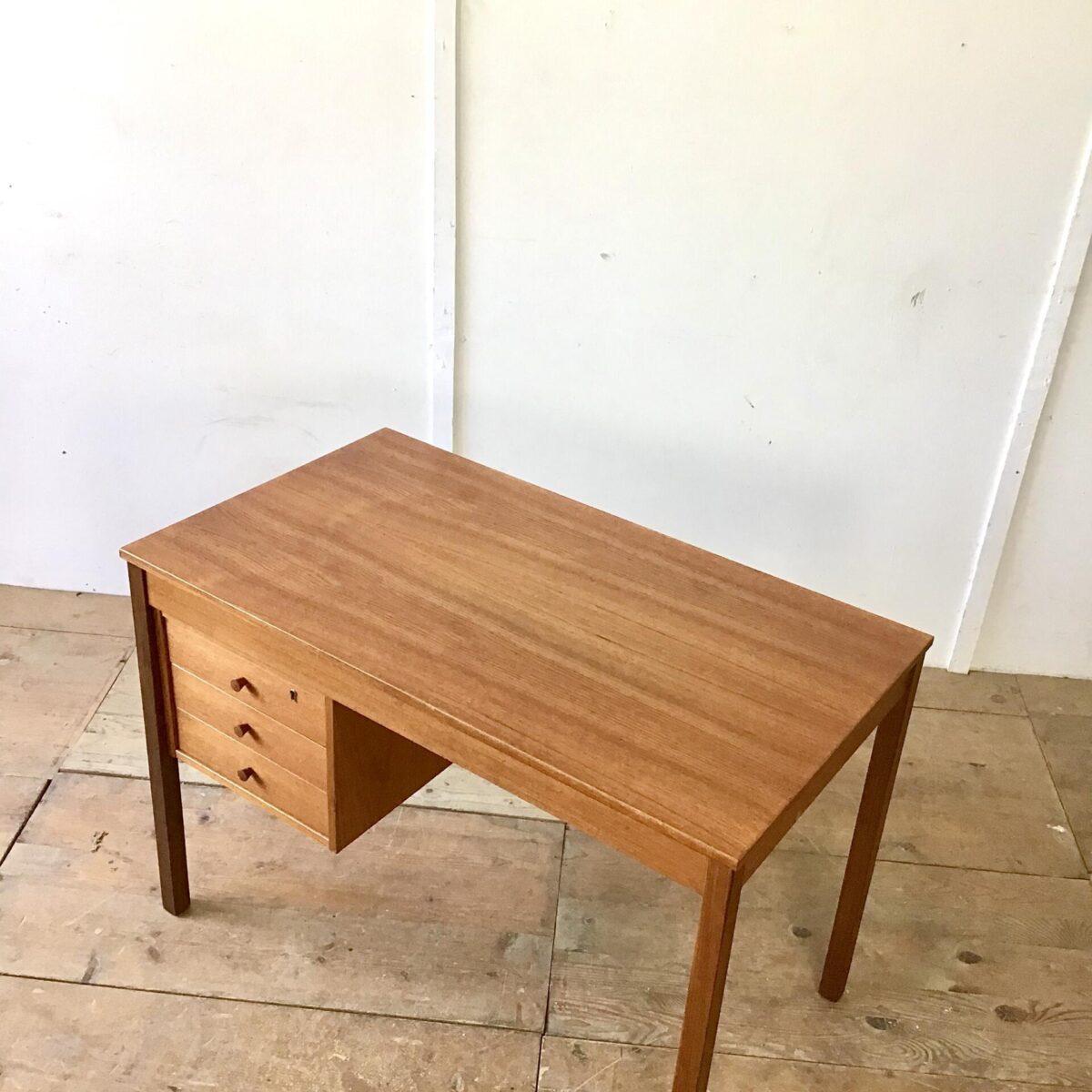 Midcentury Teak Schreibtisch mit Schubladen. 104.5cm mal 59cm Höhe 73cm. Die Tischbeine sind etwas dunkler als der Rest des Pultes. Drei Schubladen eine davon ist abschliessbar.