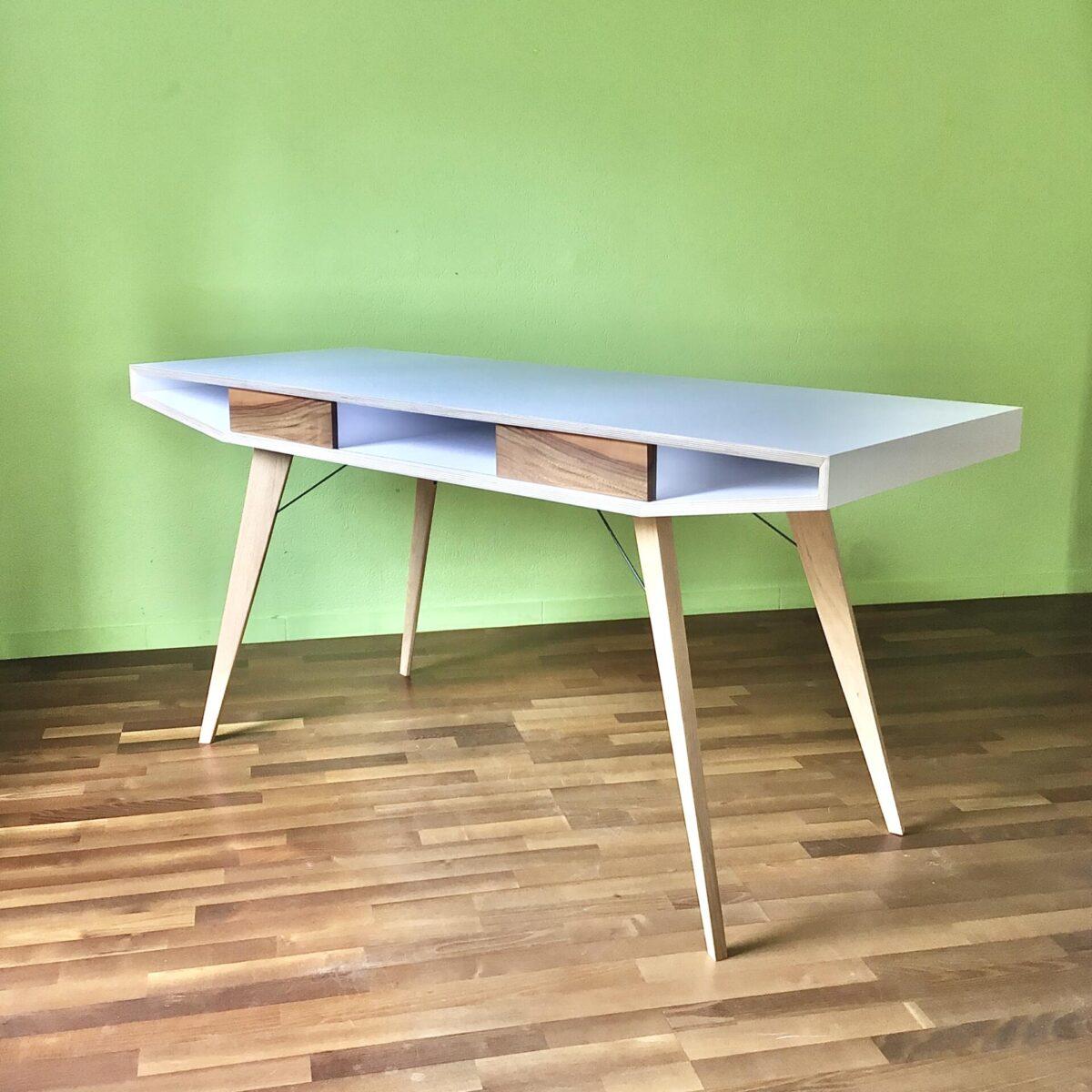 deuxieme.shop Schreibtisch 160 x 60cm Höhe 76.5cm. Der Tisch ist eine Eigenkreation, aus Birkensperrholz mit weisser Melamin Beschichtung. Tischbeine Eiche Massivholz, mit feinen Metallverstrebungen. Unter dem Tischblatt befinden sich fünf Ablagefächer. Zwei kleine Schiebetüren aus Nussbaum geben dem Tisch seinen Charakter. Dieser Schreibtisch zeichnet sich durch seine hochwertigen Materialien aus. Die weisse Tischoberfläche bietet einen ruhigen, pflegeleichten Arbeitsplatz.