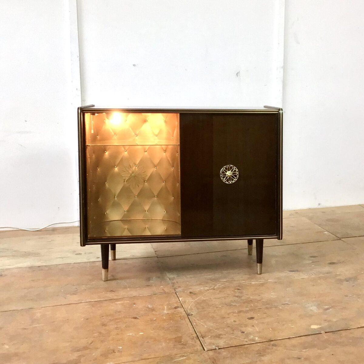 Vintage Sideboard 84.5cm mal 41cm Höhe 74cm. Hinter der Glas Schiebetür ist das Möbel mit goldigem Stoff ausgekleidet. Am Boden hat's ein Spiegel und von oben bringt eine kleine Lampe Licht in die Vitrine. Die rechte Hälfte der Kommode bietet etwas stau Raum mit einem Tablar. Der Messing Türgriff mit der Sonnen artigen Verzierung wiederholt sich bei der Glastüre, dort ist es ins hinterglas eingefräst. Oben auf dem Sideboard hat's ein paar Kratzer im Lack. Bei Füssen ist die untere, goldige Farbe teilweise abgeblättert. Ansonsten in stabilem funktionalen Zustand.