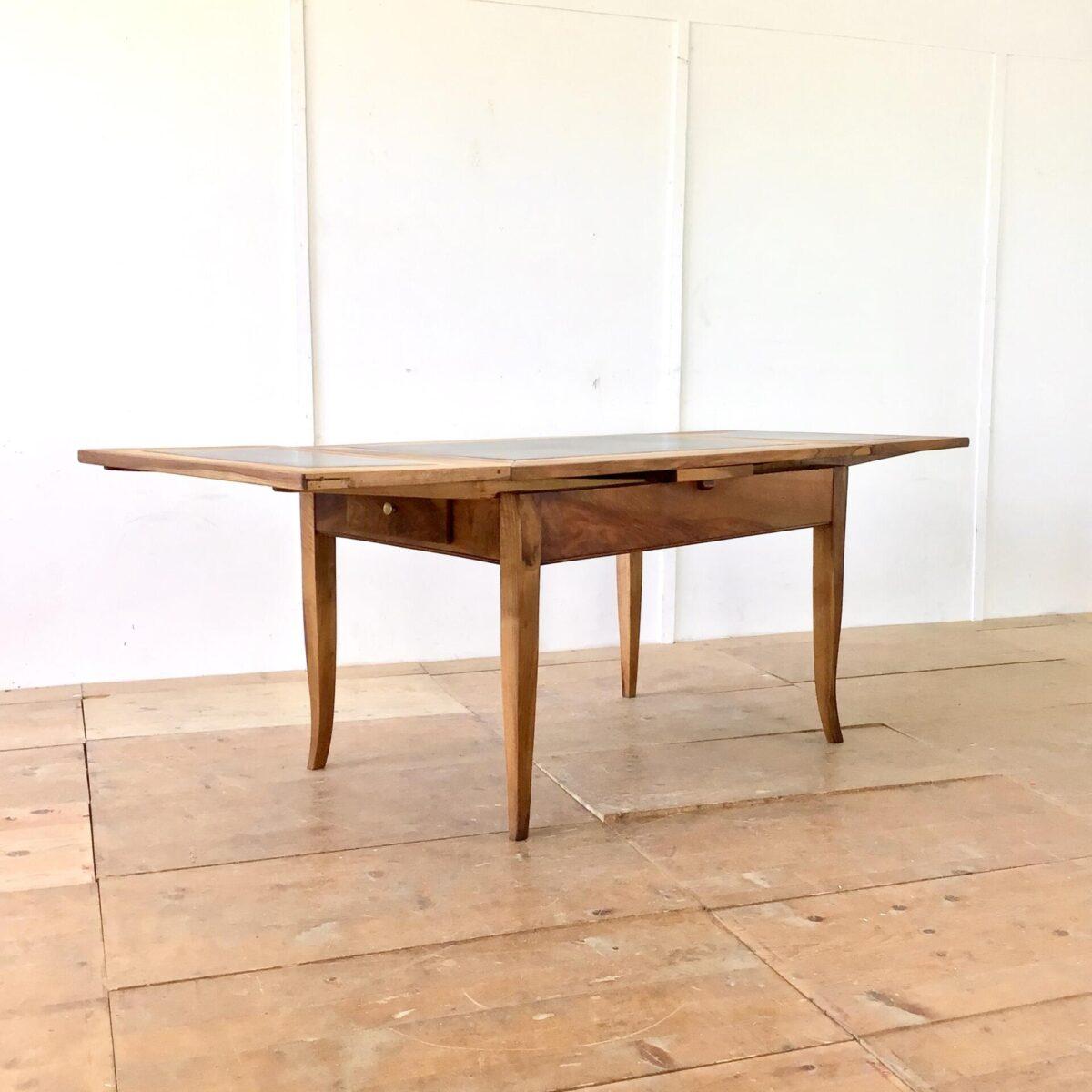 Antiker Nussbaum Schiefertisch ausziehbar. 122 x 82 Höhe 76.5cm. Ausgezogen 216 x 82cm. Warme Dunkelbraune Ausstrahlung. Die Kombination von altem Nussbaumholz, mit dem satten schwarzen Schiefer gefällt mir immer wieder. Die grosse Steinplatte hat, wie die meisten Schiefertafeln, einen Riss. Ist jedoch stabil und alltagstauglich. An der einen Stirnseite hat es ein Besteckschublade. Der Tisch ist geölt, was ihn optisch und haptisch sehr angenehm macht.