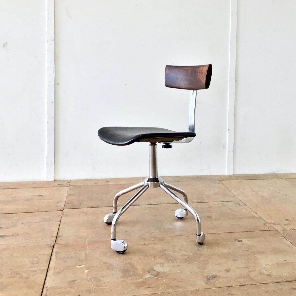 deuxieme.shop Dieser alte, feingliedrige Bürostuhl kam nur als Untergestell zu uns. Er bekam eine neue Sitzfläche aus schwarzem Leder. Die Rückenlehne ist aus Palisander Vollholz geschnitzt. Das Ziel war die Runden Formen der Füsse, oben nochmal aufzugreifen. Und Trotzdem einen eckigen, markanten Kontrast zu schaffen. Der Stuhl ist höhenverstellbar von 48-60cm.