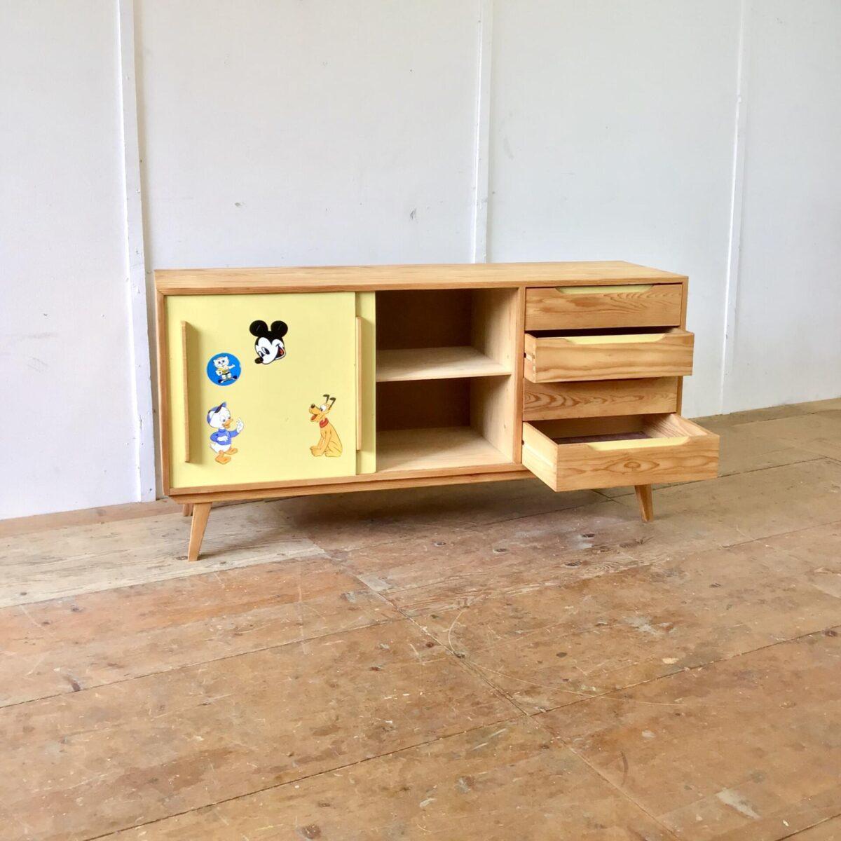 Tannenholz Sideboard aus den 60er 70er Jahren. 150x44.5cm Höhe 75cm. Die Schiebetüren sind aus gelbem Kunstharz (Kelko). Die Aufkleber aus der Zeit, lassen sich natürlich entfernen, solange nicht klar ist ob jemand Freude daran hat, bleiben Sie noch dran. Die Kommode ist proportional sehr ausgewogen und praktisch. Ob als Sideboard im Wohnzimmer mit TV Gerät, oder als Kleiderkommode im Kinderzimmer. Das Möbel ist sehr geräumig und funktional mit den Schubladen und Schiebetüren. Alle Vollholz Elemente sind geschliffen und mit Naturöl behandelt.