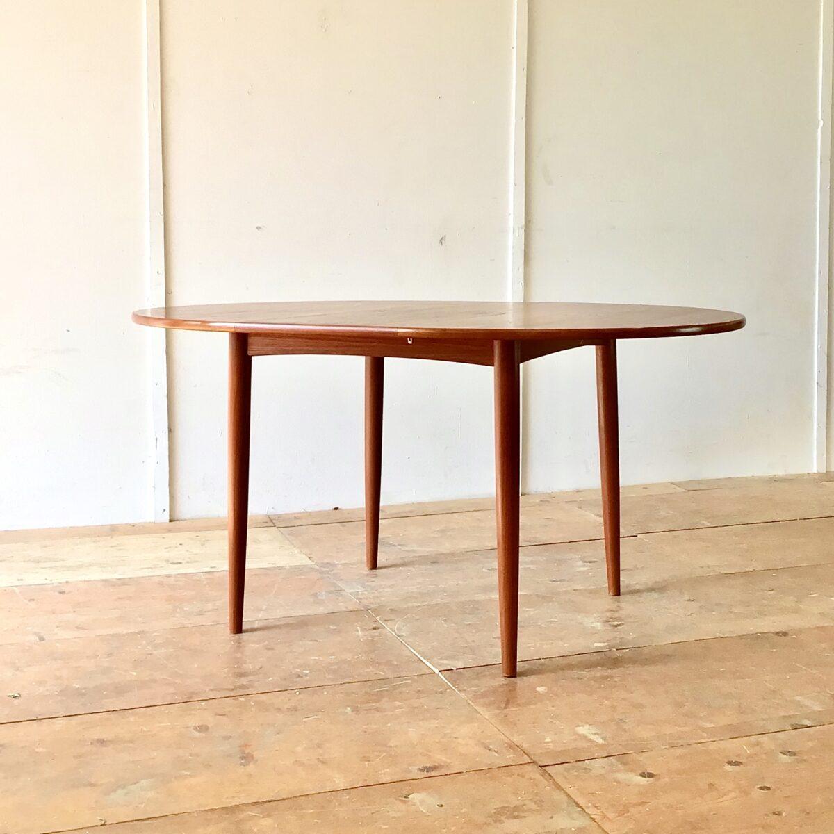 Midcentury Teak Tisch. Esstisch, Küchentisch runder Auszugtisch, Holztisch. Durchmesser 110cm Höhe 73cm ausgezogen 148 x 110cm. Tischblatt furniert geölt, ausziehbar. Die Verlängerung ist aufklappbar und lässt sich im Bauch des Tisches verstauen. Die konisch runden Tischbeine sind aus Vollholz.