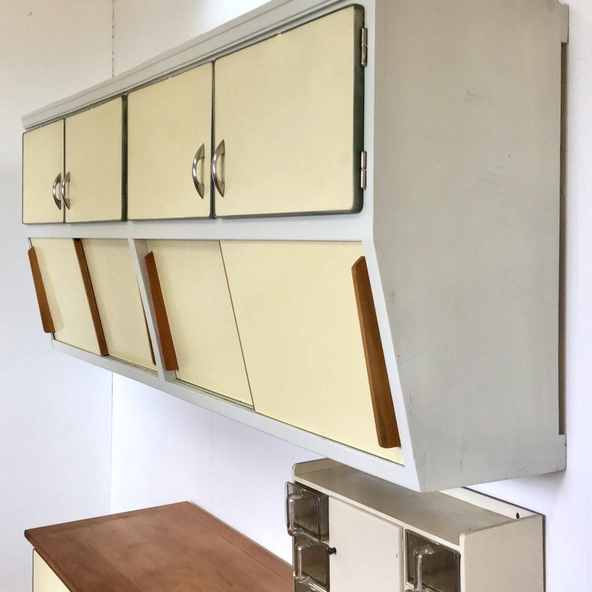 Alte Küchen Kombination frisch aufbereitet. Das Büffet ist 162x53cm Höhe 89cm. Es steht auf einem Buchenholz Sockel. Die Arbeitsplatte ist ebenfalls aus Buche Vollholz. Der lange Oberschrank ist unten, leicht nach hinten abgeschrägt. 213x43.5cm Höhe 82.5cm, die untere Tiefe misst 32cm. Die Möbel sind weiss cremig angemalt. Schubladen und Türfronten aus leicht gelblichem Kunstharz (Kelko). Kleinere Schrammen, und ein paar Absplitterungen der grünen Kunststoffumrandung sind die Zeichen der Zeit. Das Möbel ist gereinigt und in gebrauchsfertigem Zustand, die paar fehlenden Tablare werden noch ersetzt.