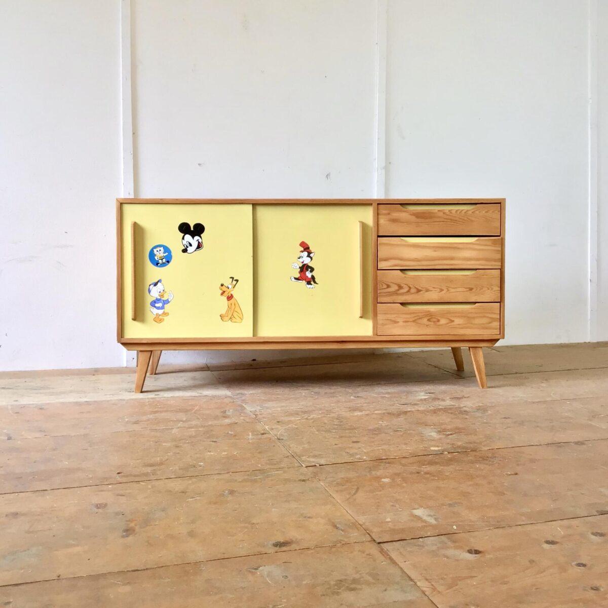 Deuxieme.shop Tannenholz Sideboard aus den 60er 70er Jahren. 150x44.5cm Höhe 75cm. Die Schiebetüren sind aus gelbem Kunstharz (Kelko). Die Aufkleber aus der Zeit, lassen sich natürlich entfernen, solange nicht klar ist ob jemand Freude daran hat, bleiben Sie noch dran. Die Kommode ist proportional sehr ausgewogen und praktisch. Ob als Sideboard im Wohnzimmer mit TV Gerät, oder als Kleiderkommode im Kinderzimmer. Das Möbel ist sehr geräumig und funktional mit den Schubladen und Schiebetüren. Alle Vollholz Elemente sind geschliffen und mit Naturöl behandelt.
