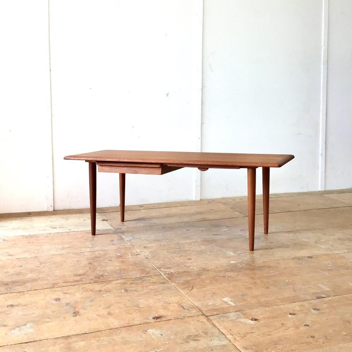 Dänischer midcentury Salontisch mit Schublade und Auszugtablar. 136x53.5cm Höhe 50cm. Der Couchtisch wurde restauriert. Teile der Schublade, welche defekt waren, haben wir neu nachproduziert. Die Holzoberflächen sind mit Naturöl behandelt. Schublade und Tablar lassen sich auf beiden Seiten ausziehen.