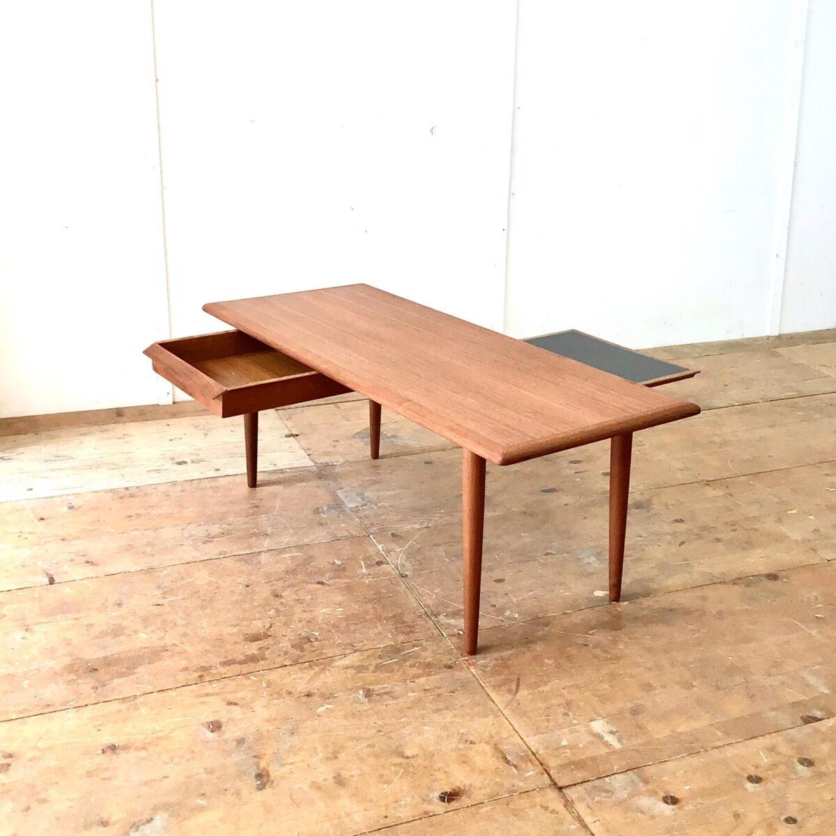 Deuxieme.shop Dänischer midcentury Salontisch mit Schublade und Auszugtablar. 136x53.5cm Höhe 50cm. Der Couchtisch wurde restauriert. Teile der Schublade, welche defekt waren, haben wir neu nachproduziert. Die Holzoberflächen sind mit Naturöl behandelt. Schublade und Tablar lassen sich auf beiden Seiten ausziehen.