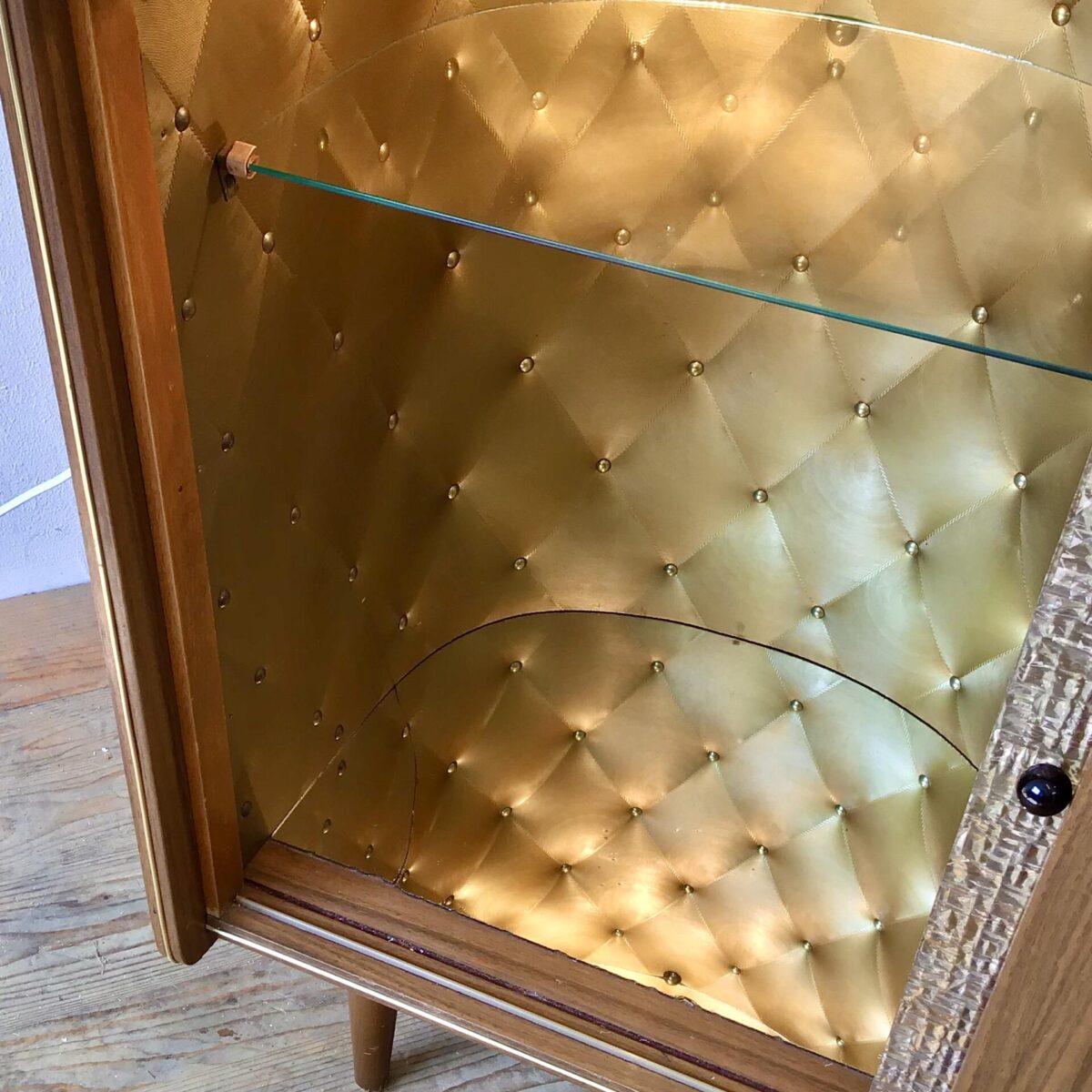 Vintage Sideboard 84.5cm x 41cm Höhe 74cm. Hinter der Plexiglas-Schiebetür ist das Möbel mit goldigem Stoff ausgekleidet. Am Boden hat es einen Spiegel und von oben bringt eine kleine Lampe Licht in die Vitrine. Die rechte Hälfte der Kommode bietet etwas Stauraum mit einem Tablar. Messing Türgriff mit sonnenartiger Verzierung. Der Spiegel auf dem Vitrinen Boden hat einen Riss und die Vorderkante ist etwas verfressen. Ansonsten in stabilem, funktionalen Zustand.