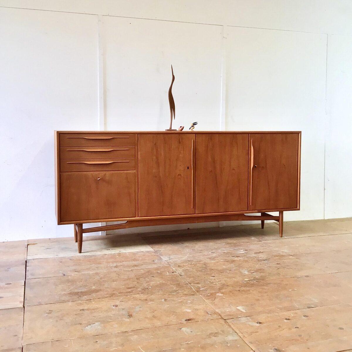 Midcentury Sideboard von swiss teak. 220x47cm Höhe 99.5cm. Grosses sehr gut erhaltenes Sideboard aus den 60er Jahren. Unaufgeregtes Design und sehr hochwertig verarbeitet. Die konischen Runden Beine mit den geschwungenen Verstrebungen gefallen mir besonders gut. Auch die halbrunden, in die Länge gezogenen, Holzgriffe sind immer wieder schön anzuschauen. Hinter den Türen hat es zwei Tablare. Unter den drei Schubladen befindet sich das Barfach, mit Klappe und geschwärztem Glas Boden. Die Kommode ist mit zwei verschiedenen Schlüsseln abschliessbar, welche detailverliebt mit holz eingefasst sind.