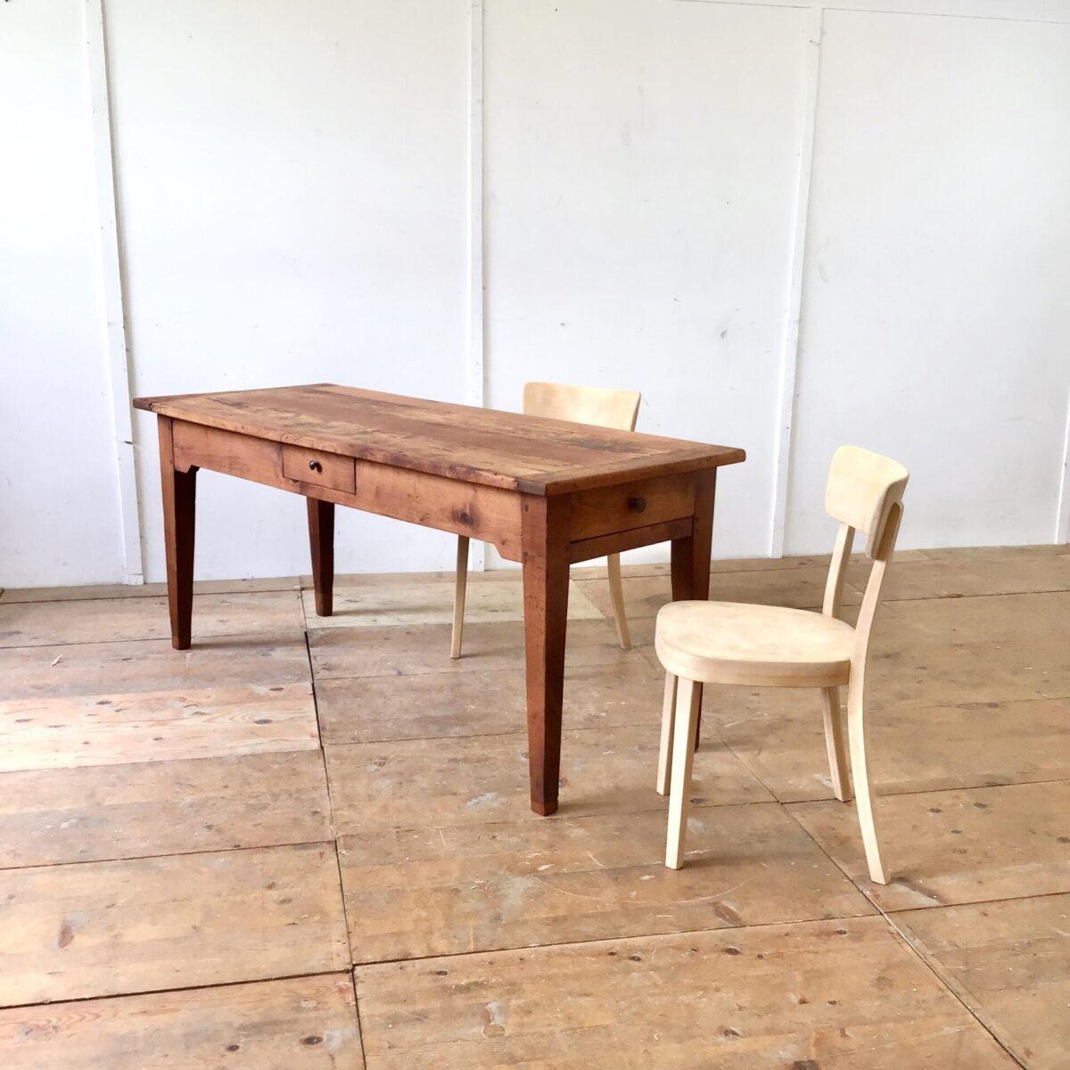 Alter französischer Kirschbaumtisch mit zwei Besteck Schubladen. 171x68cm Höhe 76cm. Verlebtes altes Kirschbaum Vollholz mit Wurmlöchern, Schrammen, Beulen und Verfärbungen. Alters bedingte, leicht unebene Tischoberfläche. Der Tisch ist komplett geschliffen und geölt. Die gröbsten Ausgefressenen Stellen haben wir mit Kirschbaum Stirnholz gefüllt. Solch altes Kirschbaumholz hat eine sehr intensive rötliche Farbe. Tischbeine wurden mal etwas angesetzt, und die Zargen etwas gestutzt um die nötige Beinfreiheit zu gewährleisten.