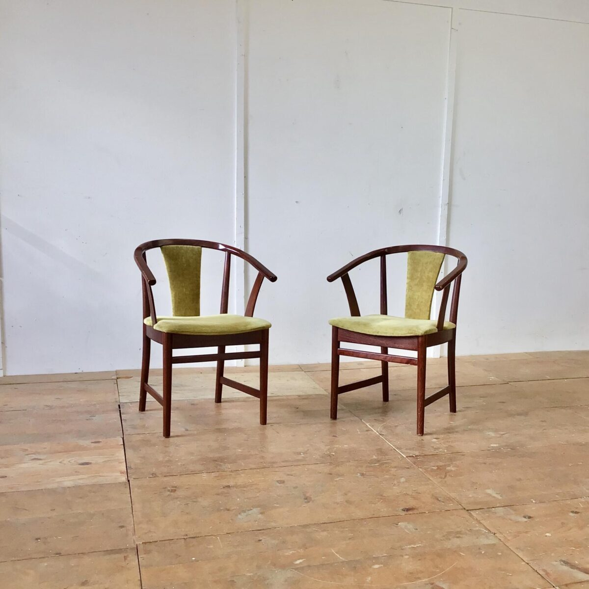 Zwei Esszimmer Stühle mit Armlehnen. Grün-gelber Samt artiger Stoff mit Polsternägel beim Rücken.