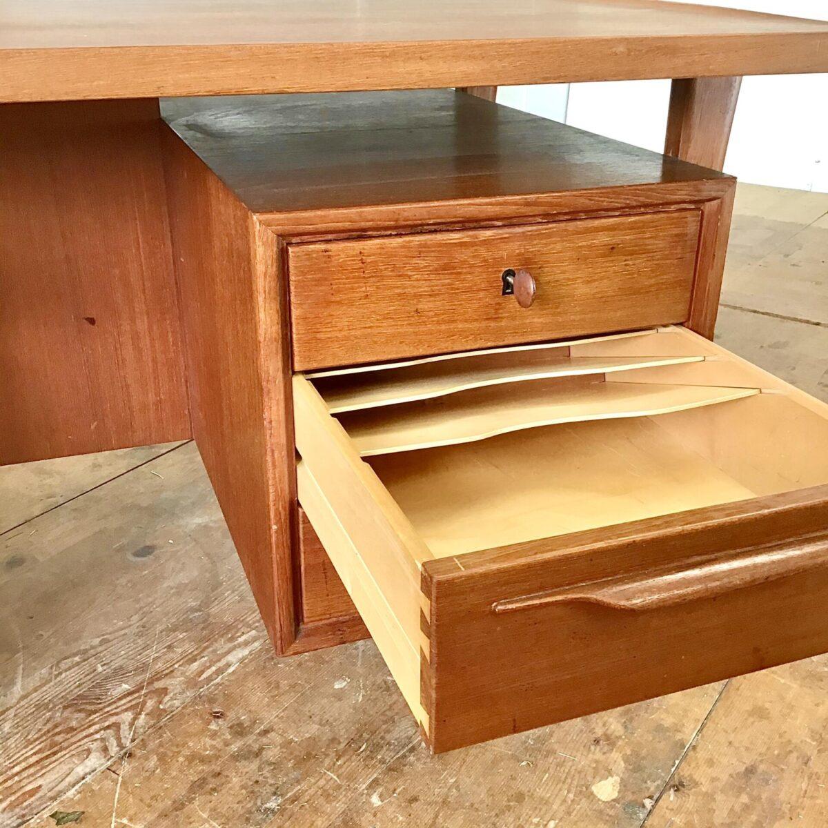 Schreibtisch mit Schubladen von Swiss Teak. 160x80cm Höhe 73cm. Das Tischblatt hat eine leicht geschwungene Grundform, die beiden Stirnseiten sind etwas noch oben gewölbt. Die Schubladen mit den schönen Griffen sind teilweise abschliessbar. Auf der Hinterseite des Tisches hat es ein Ablagefach und ist eigentlich ein Tablar vorgesehen, welches aber fehlt. Da würde sich aber auf Wunsch etwas machen lassen. Der Tisch ist in einem guten Allgemeinzustand, abgesehen von ein paar kleineren altersbedingten hicken und Schrammen.