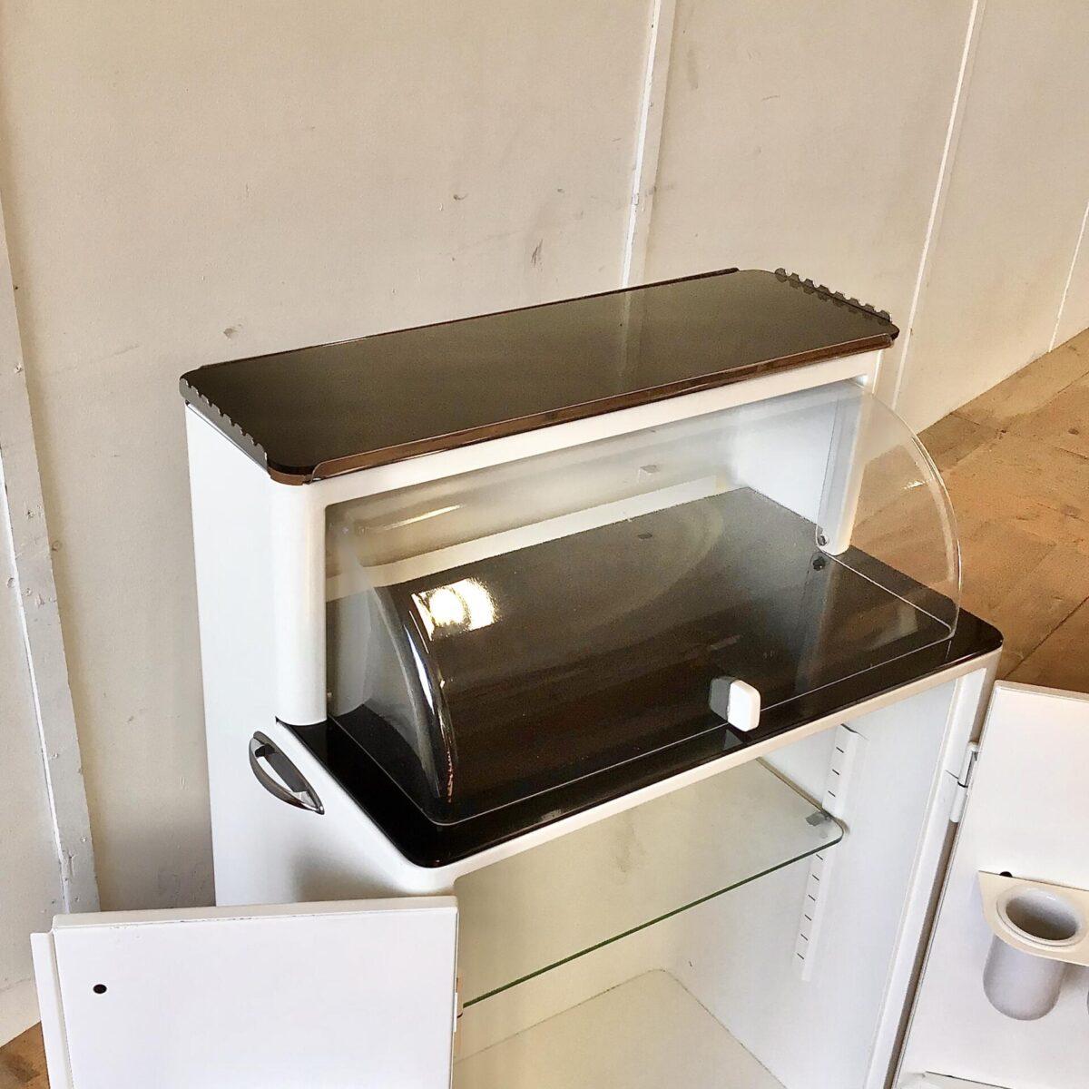 Altes Praxismöbel aus Metall. 70x41cm Höhe 116cm, die untere Arbeitsfläche ist auf 91.5cm Höhe. Das Möbel kann recht vielseitig eingesetzt werden, ob als Barschrank, Sideboard oder Vitrine um etwas Auszustellen. Der Arztschrank steht auf vier Schwenkbaren Möbelrollen. Das Metall ist weiss lackiert, griffe verchromt. Die Ablageflächen sind aus geschwärztem Glas. Die Runde, Brotkasten ähnliche, Haube ist aus Plexiglas mit Kunststoffgriff. Hinter den Schranktüren befinden sich Tablare, zwei herausnehmbare Keramik Gläser und Flaschenhalter.