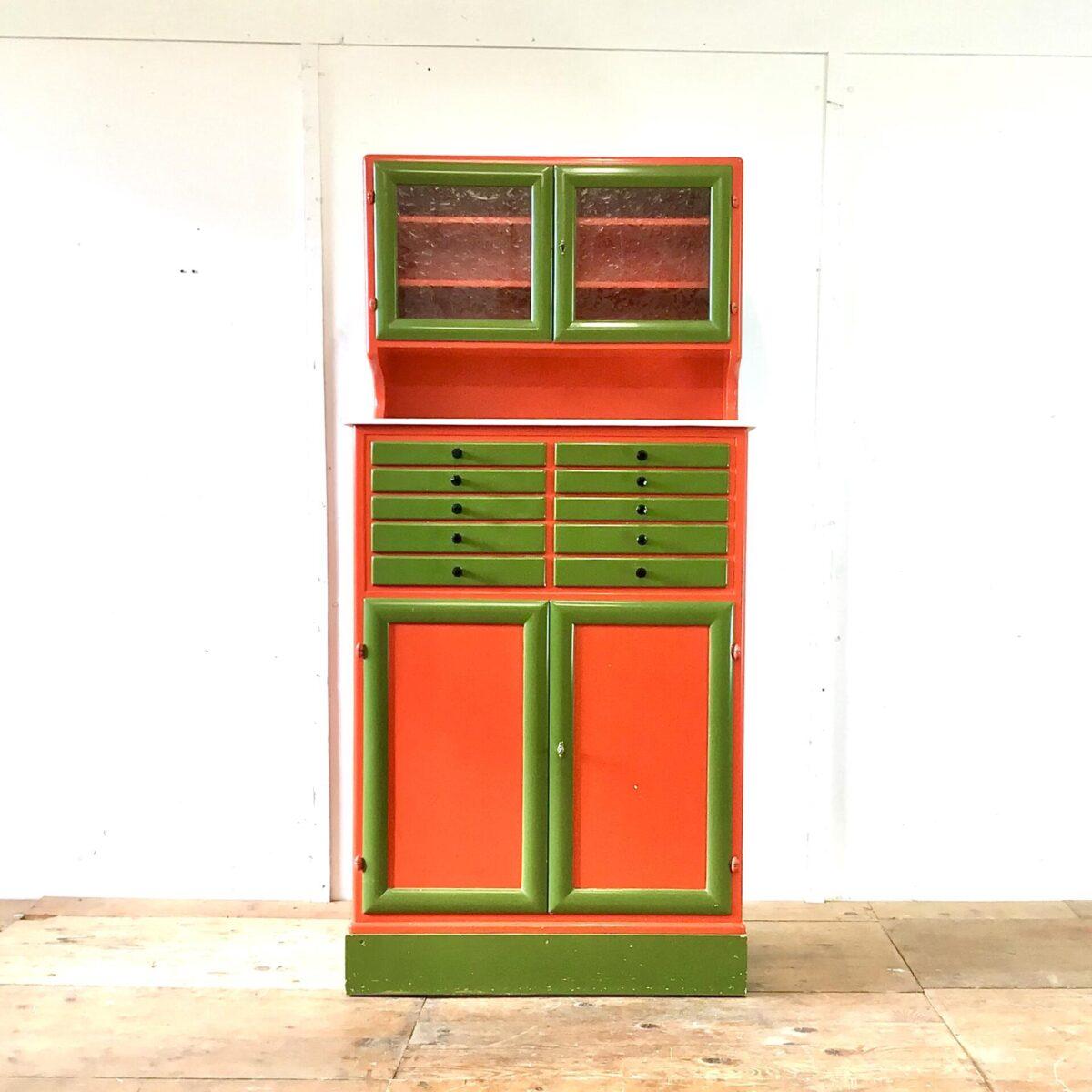 Farbiges Vintage Buffet mit Schubladen. 82x38cm Höhe 169.5cm. Die weisse Marmor ähnliche Ablagefläche, wohl aus Kunststein, ist 114.5cm ab Boden. Das Möbel ist ähnlich einem klassischen Küchenbuffet aufgebaut. Dient aber wohl eher einem Wohnzimmer Schrank da die Arbeitsfläche höher ist. Der Oberschrank hat gemusterte Glastüren. Hinter den unteren Türen findet man Stauraum mit drei Tablaren. Die Türen sind abschliessbar, zwei Schlüsse vorhanden. Das Herzstück sind natürlich die Schubladen mit den schwarzen Kunststoffgriffen. Ein besonders gelungenes Detail finde ich die kleinen, ovalen Scharniere.