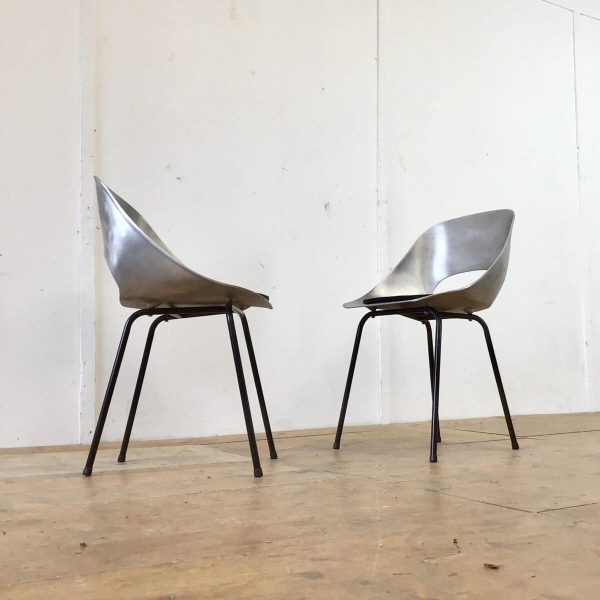 Zwei Aluminium Stühle mit schwarzen Metallfüssen. Die Schalensitze sind aus massivem ca. 3mm dicken Aluminium. Hersteller und Produktionsverfahren unbekannt. Wenn man sich aufrecht reinsetzt sind die Stühle auch bequem. Die Lehne dürfte etwas weiter nach hinten geneigt sein. Optisch sehen die Schalen mit den Löchern, und der matten Oberfläche, aber sehr hochwertig und eigenwillig aus. Sie würden sich dank den wetterbeständigen Materialen auch für draussen eignen.