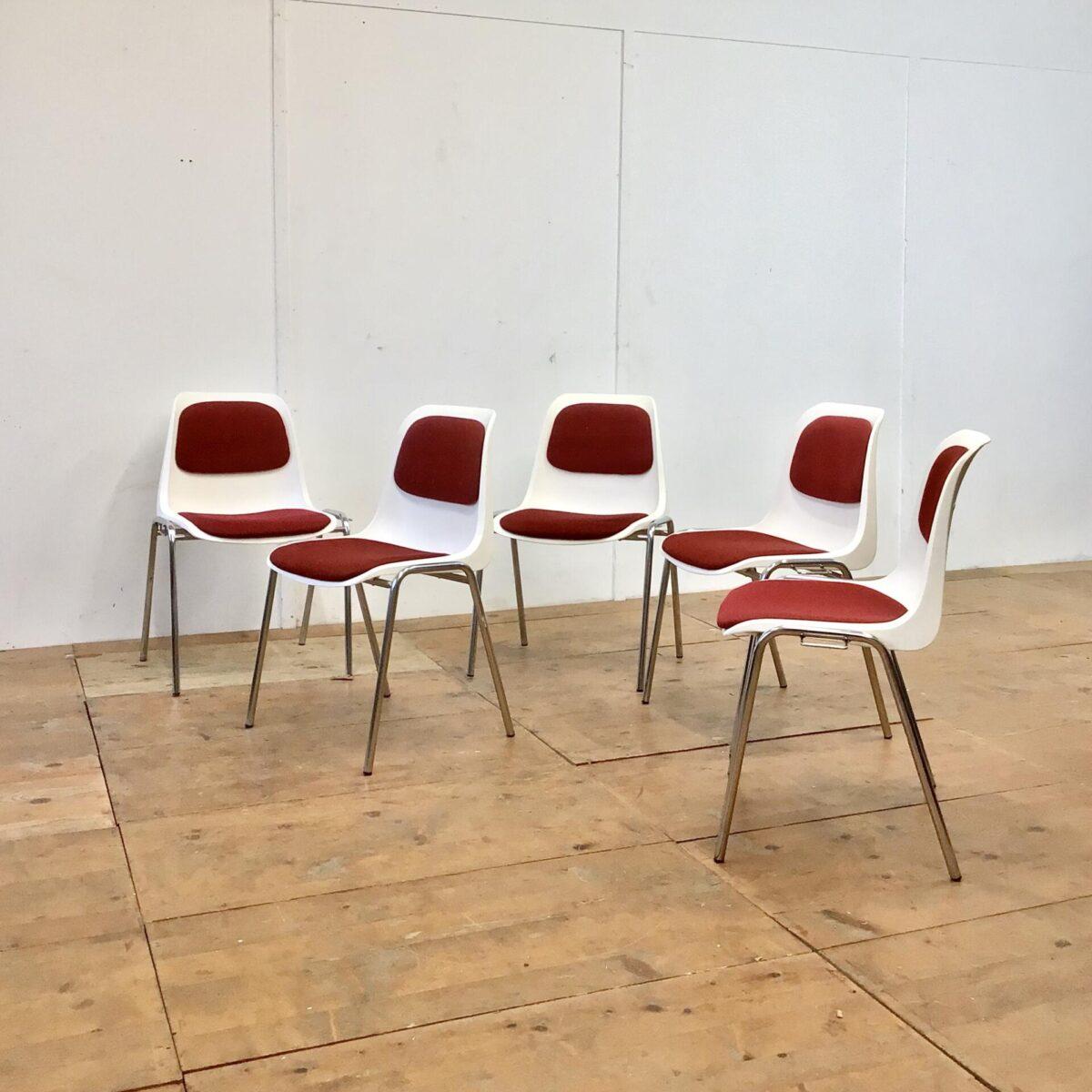 Deuxieme.shop 30 Schalenstühle von Helmut Starke. Preis pro Stuhl. Weisse Kunststoff Sitzschalen mit rotem Polster und verchromten Metall Gestell. Diese Stühle lassen sich seitlich zusammen verbinden, wie dies feuertechnisch bei einer Saalbestuhlung erforderlich ist. Für den Privaten Gebrauch lassen sich die Verbindungsbeschläge Sicherlich entfernen. Ein paar wenige sind schon ohne diese Konstruktion. Der rote Stoff Bezug ist in recht gepflegtem Zustand. Die Stühle sind recht bequem, und passen sich durch die leichte Flexibilität, dem Benutzer an.