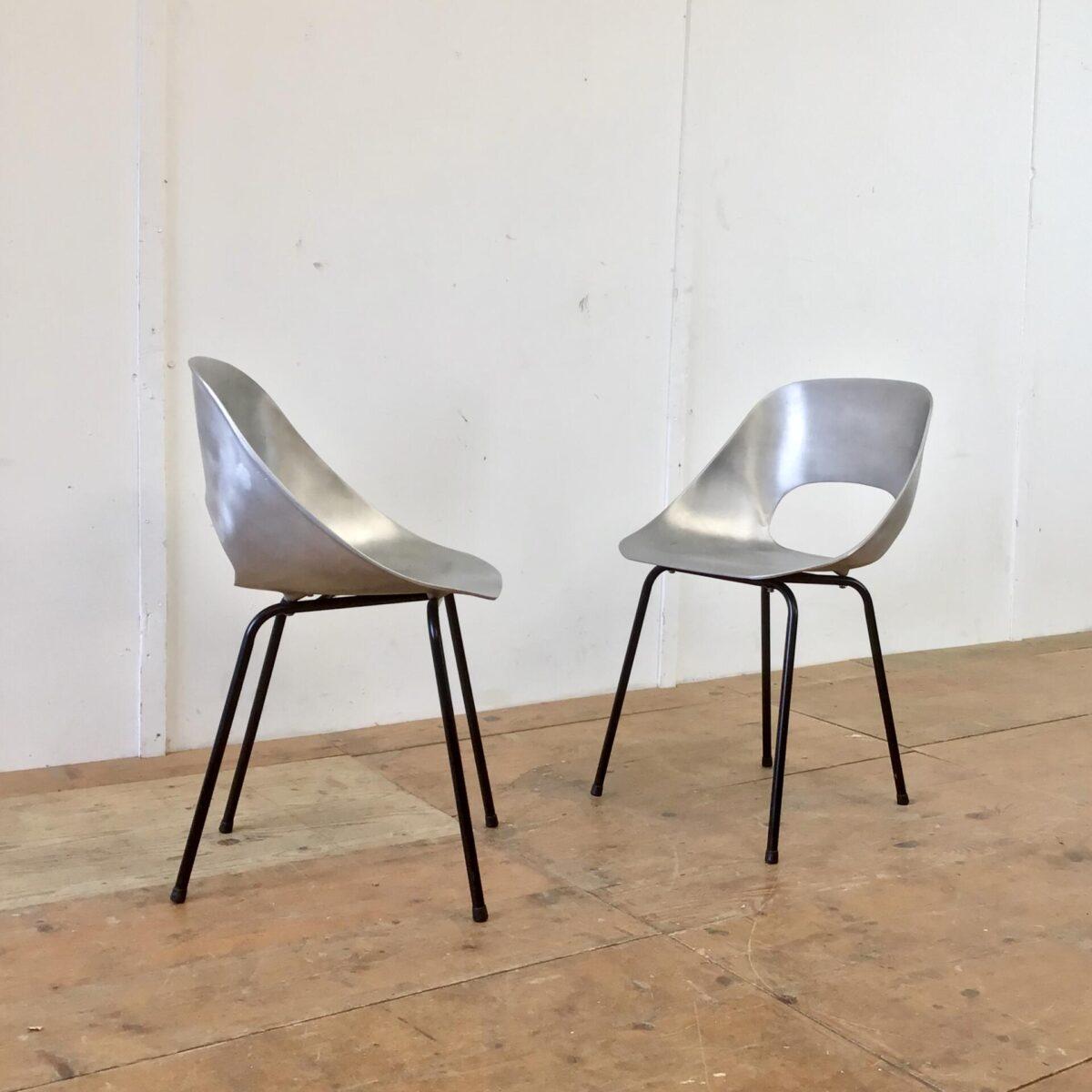 Deuxieme.shop Zwei Aluminium Stühle mit schwarzen Metallfüssen. Die Schalensitze sind aus massivem ca. 3mm dicken Aluminium. Hersteller und Produktionsverfahren unbekannt. Wenn man sich aufrecht reinsetzt sind die Stühle auch bequem. Die Lehne dürfte etwas weiter nach hinten geneigt sein. Optisch sehen die Schalen mit den Löchern, und der matten Oberfläche, aber sehr hochwertig und eigenwillig aus. Sie würden sich dank den wetterbeständigen Materialen auch für draussen eignen.