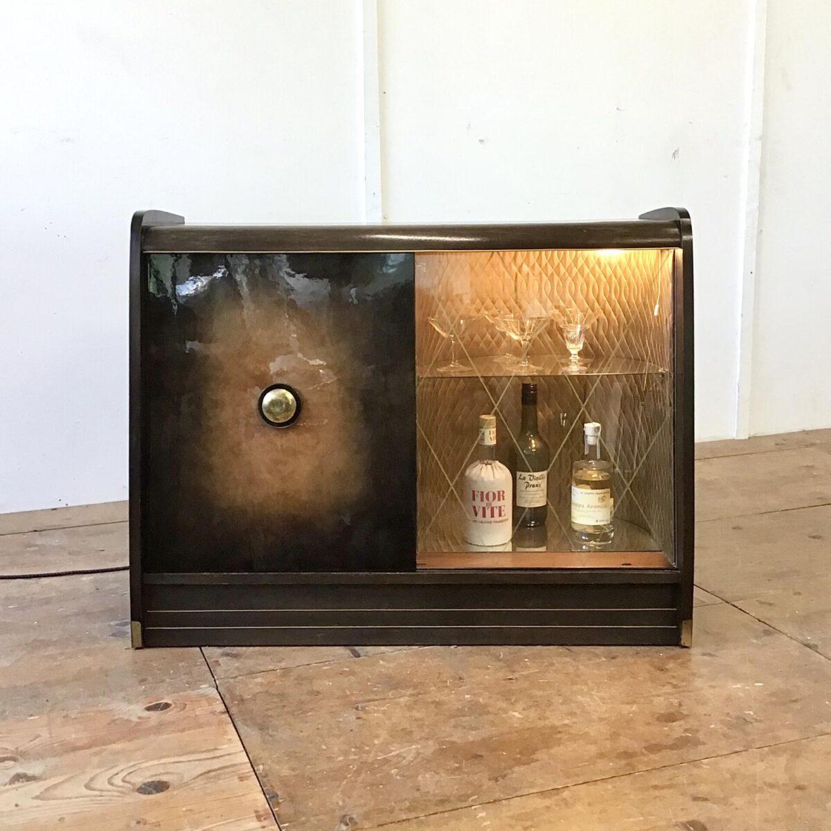 Deuxieme.shop Vintage Kommode aus den 50er 60er Jahren. 98x45,5cm Höhe 77cm. Das Sideboard hat auf der linken Seite etwas Stauraum mit einem Tablar. Rechts hinter der Glas Schiebetür befindet sich das Barfach. Gold ausgekleidet mit glas Tablar und Boden Spiegel. Diese Seite kann mit einer Lampe beleuchtet werden.