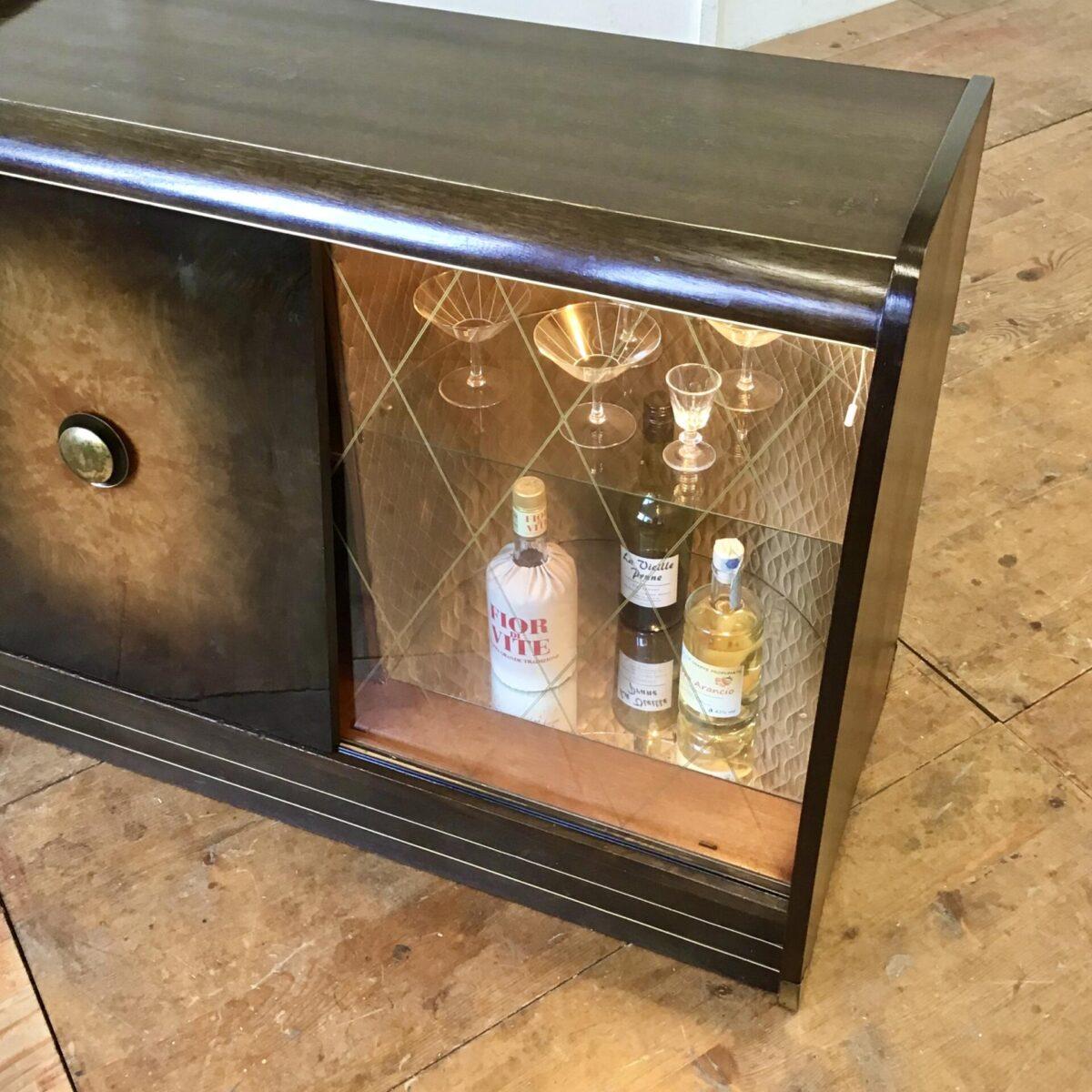 Vintage Kommode aus den 50er 60er Jahren. 98x45,5cm Höhe 77cm. Das Sideboard hat auf der linken Seite etwas Stauraum mit einem Tablar. Rechts hinter der Glas Schiebetür befindet sich das Barfach. Gold ausgekleidet mit glas Tablar und Boden Spiegel. Diese Seite kann mit einer Lampe beleuchtet werden.