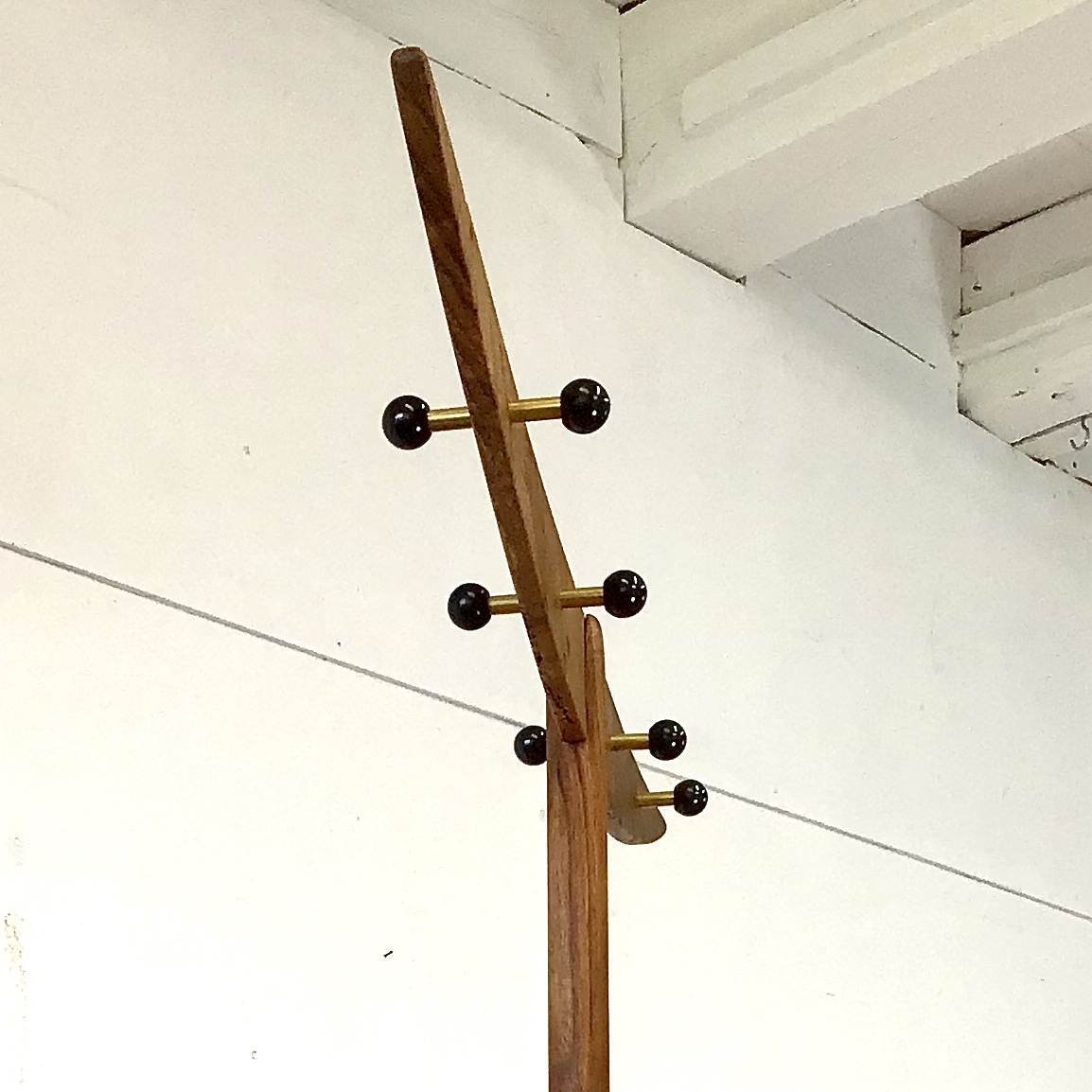 Freistehende Garderobe aus Nussbaumholz, mit Schirmständer. Dieser Kleiderständer war, bevor er zu uns kam, ein Ständer um Wolle aufzuwickeln. Wir haben das etwas neu interpretiert und arrangiert. Das ganze hatte eine relativ rustikal geschnitzte Oberfläche, welche wir etwas zeitgemässer geglättet haben. Das Mitteltablar bekam drei Schirmhalter Löcher. Oben bekam er die Sichel ähnliche, geschwungene Querstrebe. Ebenfalls aus altem Nussbaumholz. Schwarze Bakelit Kugeln auf beiden Seiten bilden die Kleiderhaken. Zwei kleine Hohlkerben bieten die Möglichkeit ein Kleiderbügel hinzuhängen.