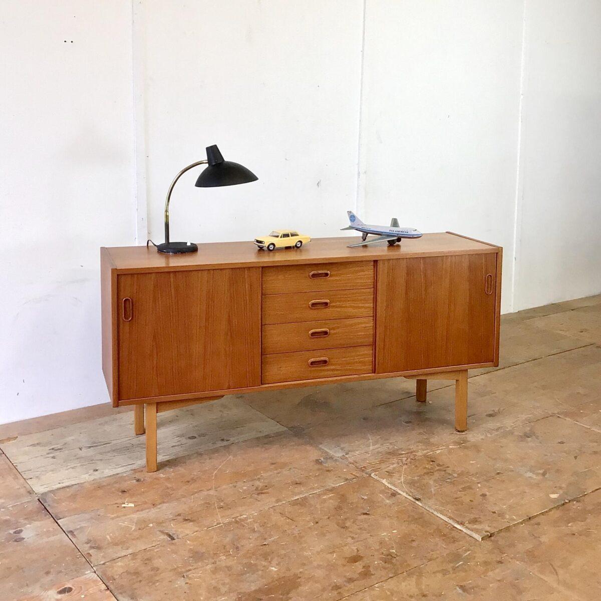 Midcentury Teak Sideboard aus den 60er Jahren 150x42cm Höhe 74cm. Schlichtes Symmetrisches Möbel mit Schiebetüren und Schubladen, in gutem Zustand. Hinter den Schiebetüren befindet sich je ein Tablar. Die eckigen geraden Beine heben das Möbel schön vom Boden ab. Proportional sehr stimmig wie ich finde.