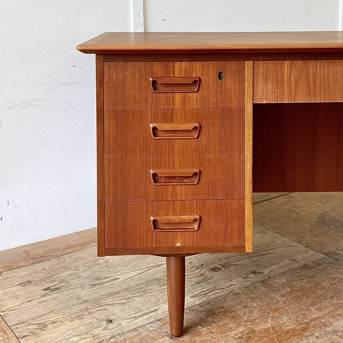 Midcentury Teak Schreibtisch 135x73cm Höhe 74cm. Dieser Tisch ist in gepflegtem guten Zustand. Zwei Schubladen und die Türe sind abschliessbar. Die Rückseite mit Tablar ist ebenfalls schön verarbeitet.