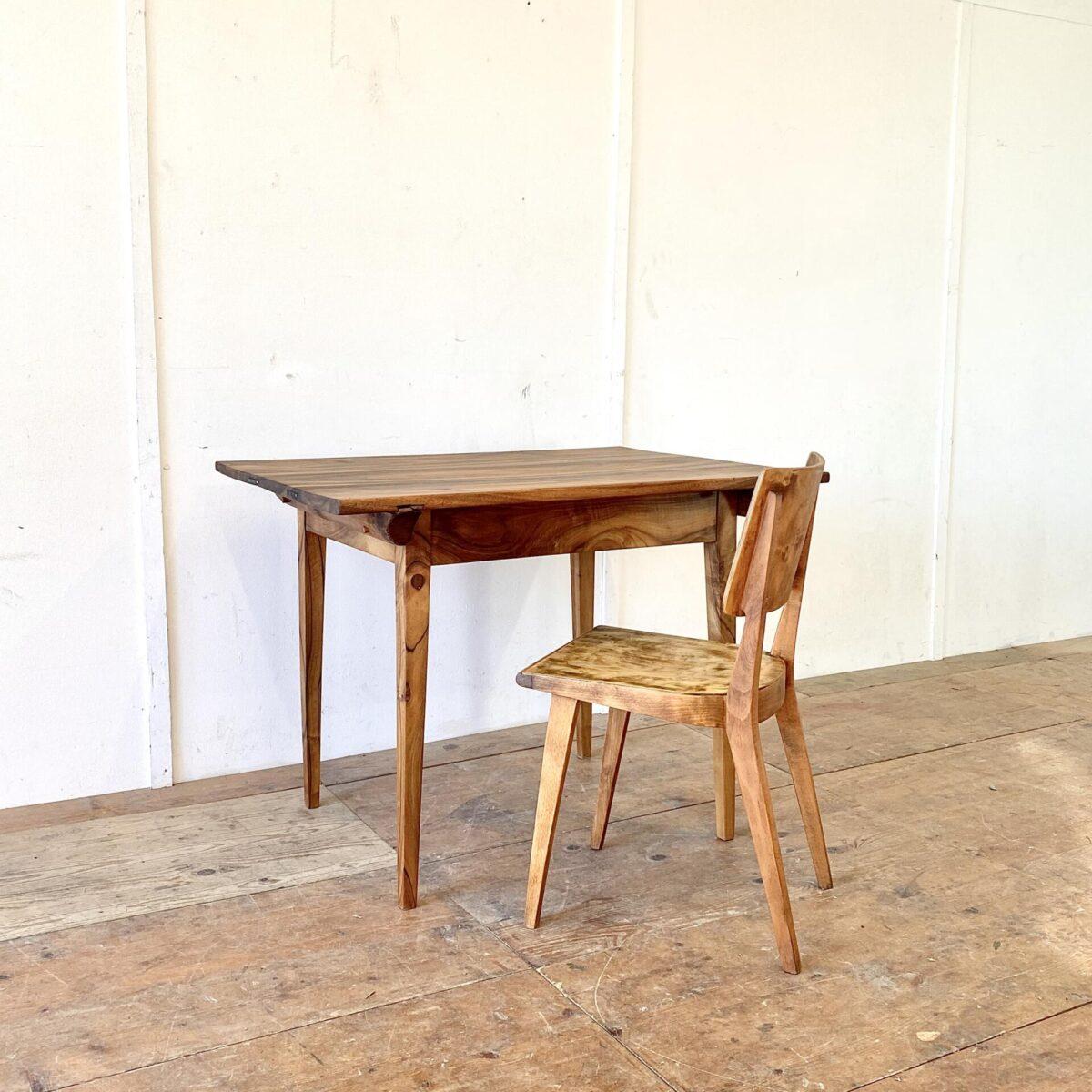 Deuxieme.shop Kleiner Nussbaum Biedermeiertisch aus Nussbaumholz. 104x78cm Höhe 75.5cm. Dieser Schreibtisch oder Küchentisch hat eine satte lebhafte Holzmaserung. Das Tischblatt bestehend aus drei breiten brettern hat ein paar eingesetzte Flicke. An den Stirnseiten sind die Leimfugen mit Metallklammern verstärkt. Die abnehmbare Tischplatte ist mittels Holzzapfen mit dem Unterbau verbunden. Die Holzoberflächen sind mit Naturöl behandelt.