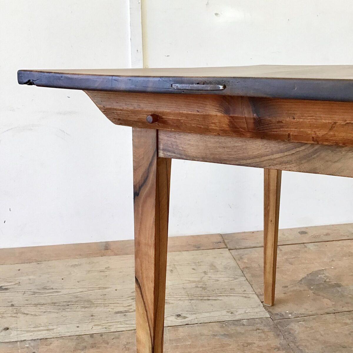 Kleiner Nussbaum Biedermeiertisch aus Nussbaumholz. 104x78cm Höhe 75.5cm. Dieser Schreibtisch oder Küchentisch hat eine satte lebhafte Holzmaserung. Das Tischblatt bestehend aus drei breiten brettern hat ein paar eingesetzte Flicke. An den Stirnseiten sind die Leimfugen mit Metallklammern verstärkt. Die abnehmbare Tischplatte ist mittels Holzzapfen mit dem Unterbau verbunden. Die Holzoberflächen sind mit Naturöl behandelt.