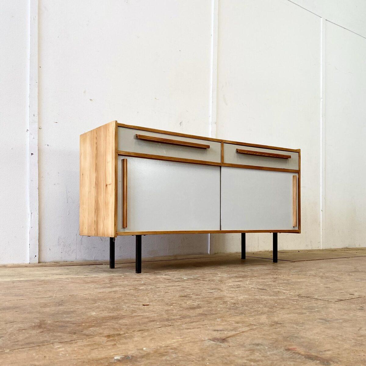 Helles Tannenholz Sideboard mit Schiebetüren und Schubladen. 120x40cm Höhe 67cm. Die Kommode steht auf schwarz lackierten Metallfüssen. Die Holzelemente sind geschliffen und geölt. Die Farbe der Schiebetüren sind leicht heller als die Schubladenfronten.