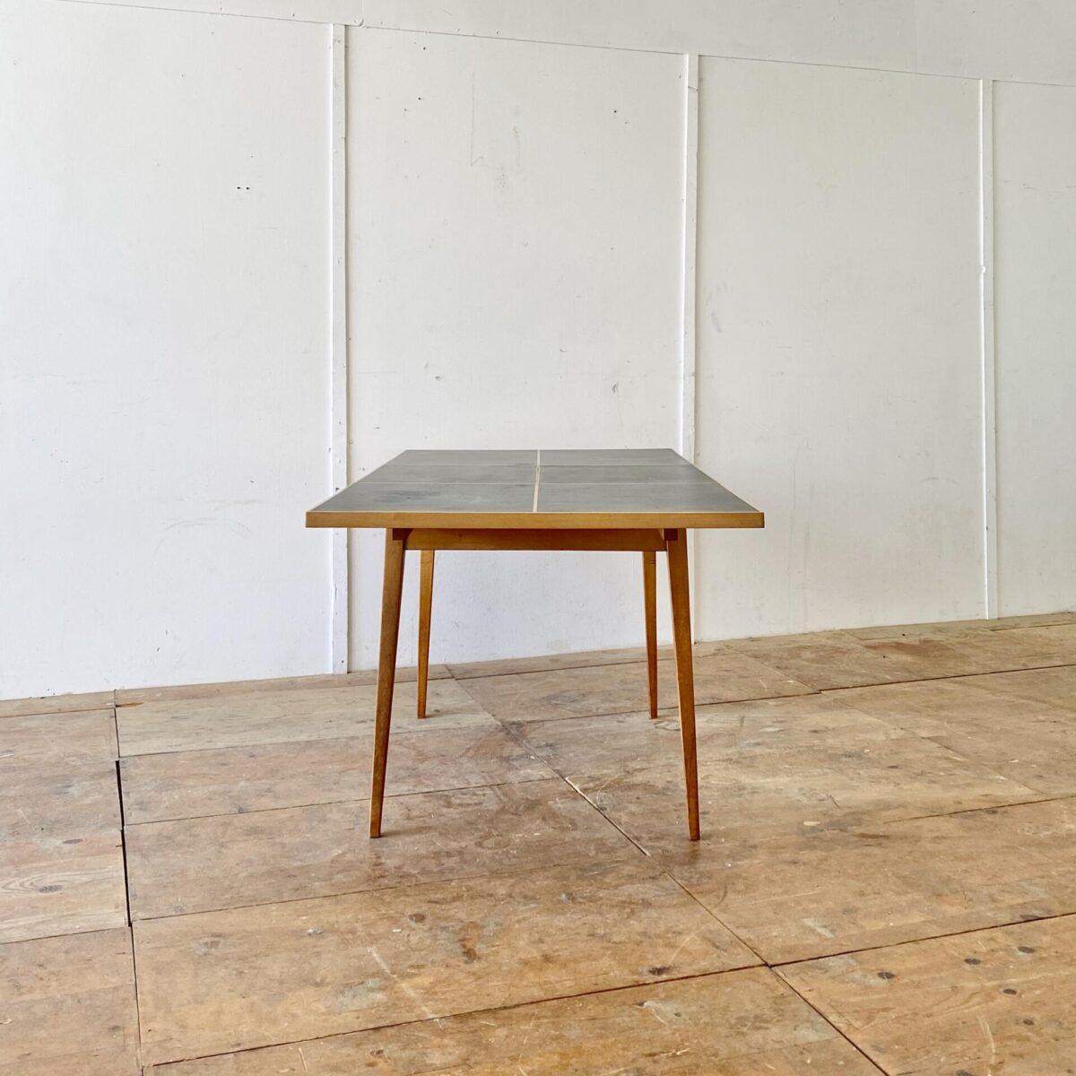 Auszugtisch aus Ahornholz mit schwarzem Linoleum. 116.5x84.5cm Höhe 72.5cm Ausgezogen 170cm lang. Hersteller nicht ersichtlich, erinnert bisschen an den Hans Bellmann Tisch von horgenglarus, aus den 50er Jahren. Das Linoleum hat ein paar kleinere Hicke und Schrammen. Das Tischgestell mit Alterspatina ist teilweise frisch verleimt und stabil.