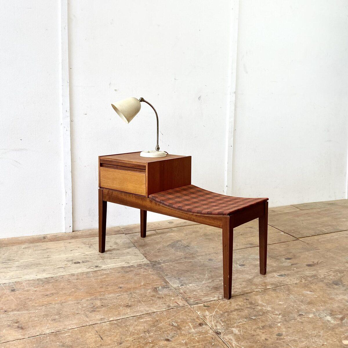 Deuxieme.shop Midcentury Teak Telefontisch mit Sitzbank. Dieses kleine Sideboard hat ein Fach mit Klappe. Das Auszugtablar hat eine weisse Beschichtung um ein paar Nummern drauf zu schreiben. Die Sitzschale ist mit einem braun-orange karierten Stoff bezogen.