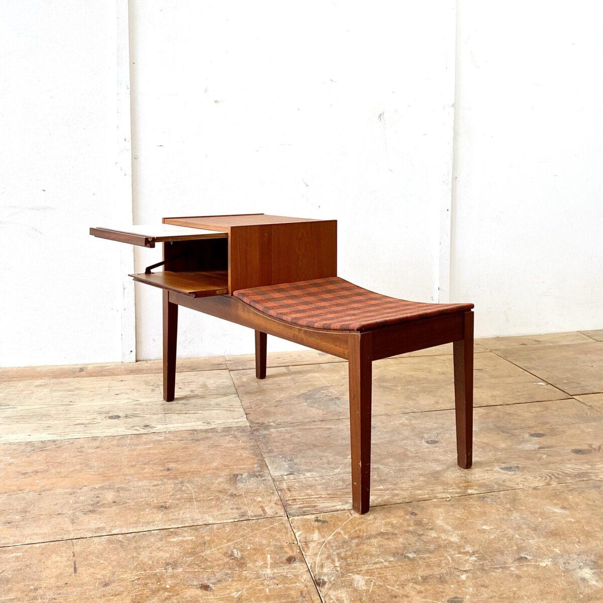 Midcentury Teak Telefontisch mit Sitzbank. Dieses kleine Sideboard hat ein Fach mit Klappe. Das Auszugtablar hat eine weisse Beschichtung um ein paar Nummern drauf zu schreiben. Die Sitzschale ist mit einem braun-orange karierten Stoff bezogen.