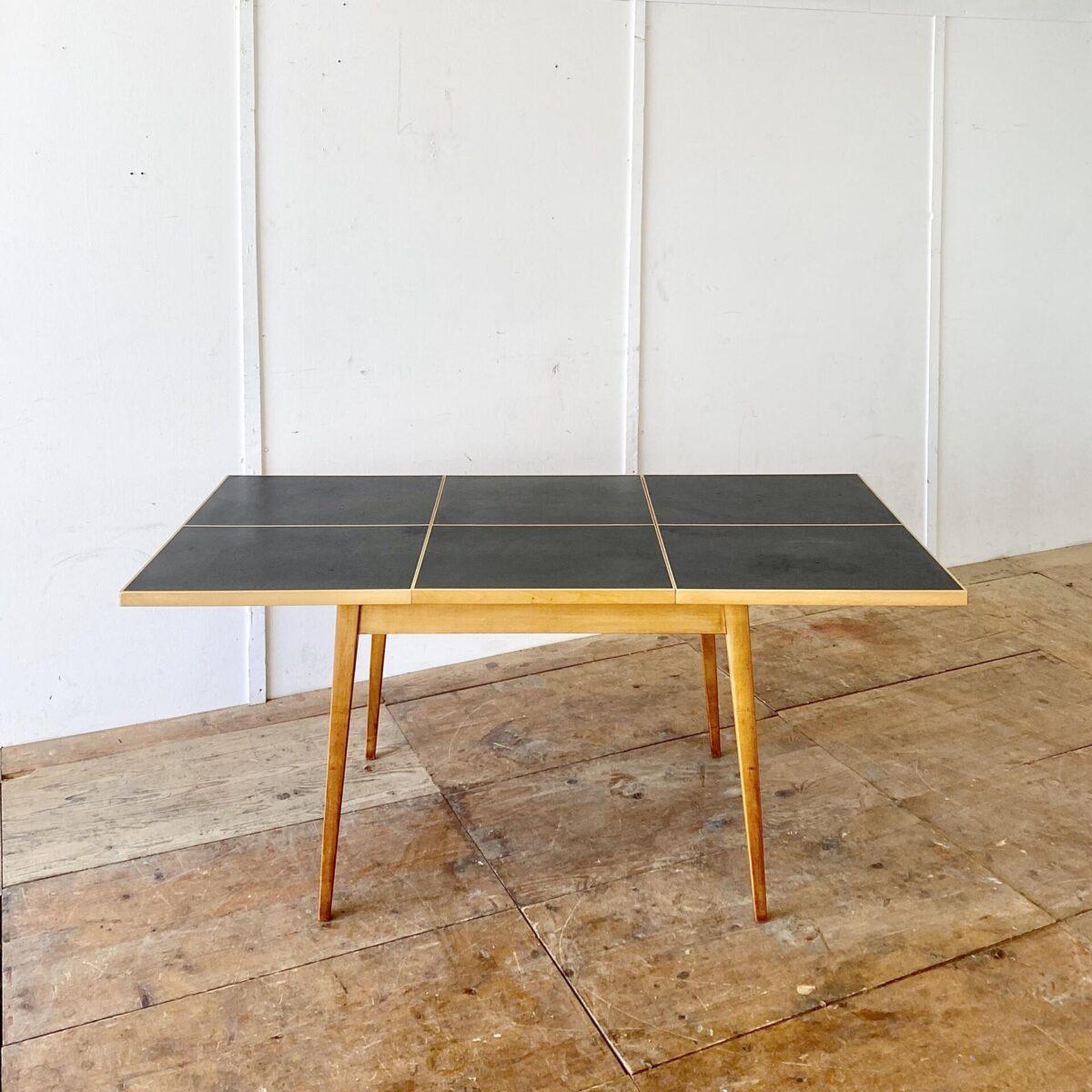 Deuxieme.shop Auszugtisch aus Ahornholz mit schwarzem Linoleum. 116.5x84.5cm Höhe 72.5cm Ausgezogen 170cm lang. Hersteller nicht ersichtlich, erinnert bisschen an den Hans Bellmann Tisch von horgenglarus, aus den 50er Jahren. Das Linoleum hat ein paar kleinere Hicke und Schrammen. Das Tischgestell mit Alterspatina ist teilweise frisch verleimt und stabil.