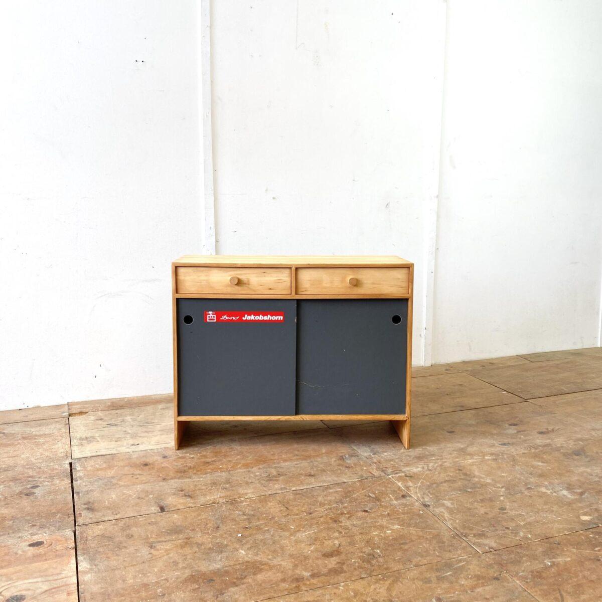 Deuxieme.shop Vintage Schiebetüren Schränkli aus den 60er 70er Jahren. 88x34cm Höhe 70.5cm. Der Schuhschrank ist aus Tannenholz, die Holzoberflächen sind geschliffen und geölt. Die Pavatex Schiebetüren mit grauer Kelko Beschichtung. Eine Türe hat eine Bruchstelle welche aber stabil ist, oder ausgewechselt werden kann. Die zwei Schubladen laufen einwandfrei.