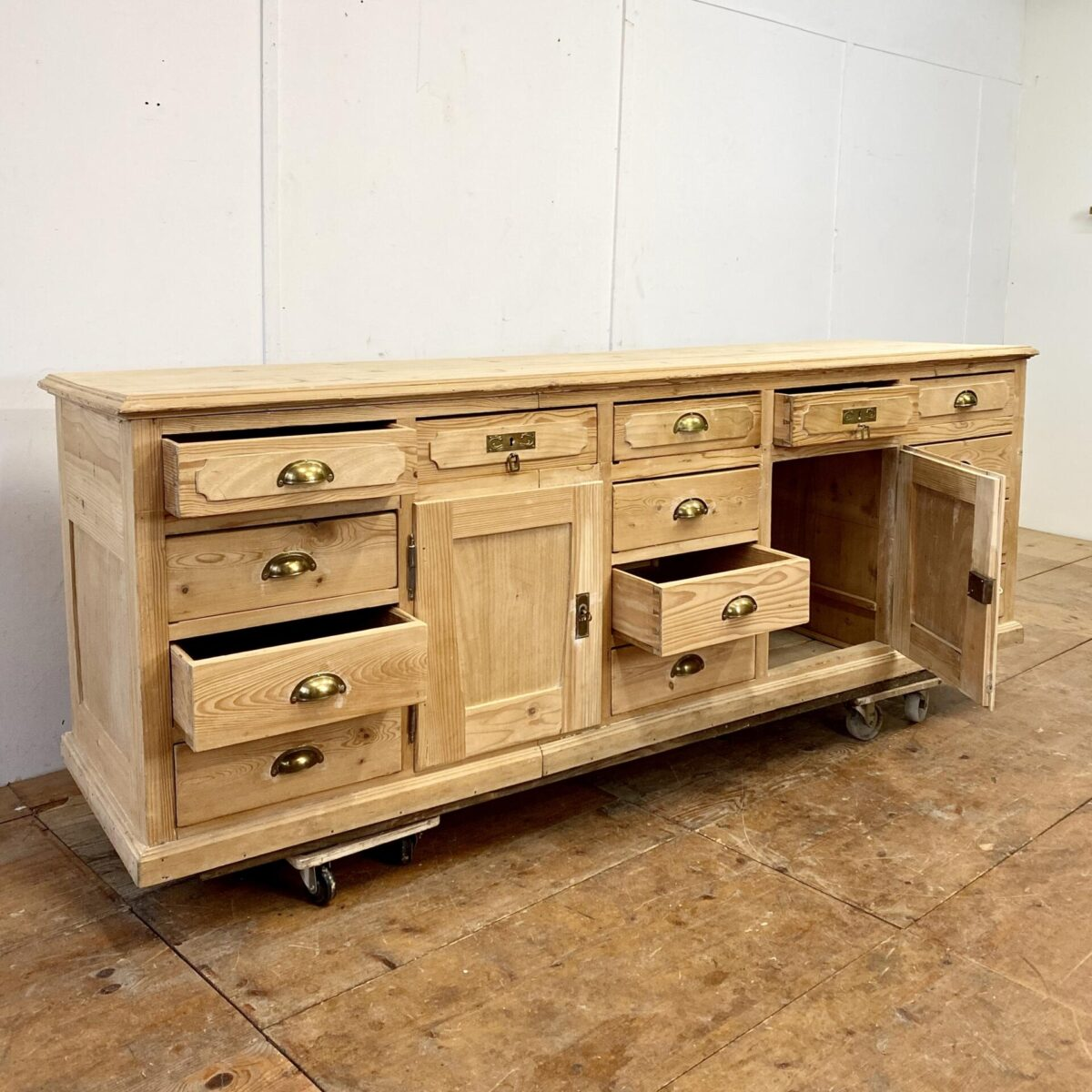 Antikes Tannenholz Schubladenmöbel. 234x65cm Höhe 81cm. Die Schubladen mit den Muschelgriffen laufen alle gut. Dieser Schubladenkorpus hat auch eine schöne Rückseite mit Füllungen. Und kann somit auch als freistehende Theke, oder Kücheninsel verwendet werden.