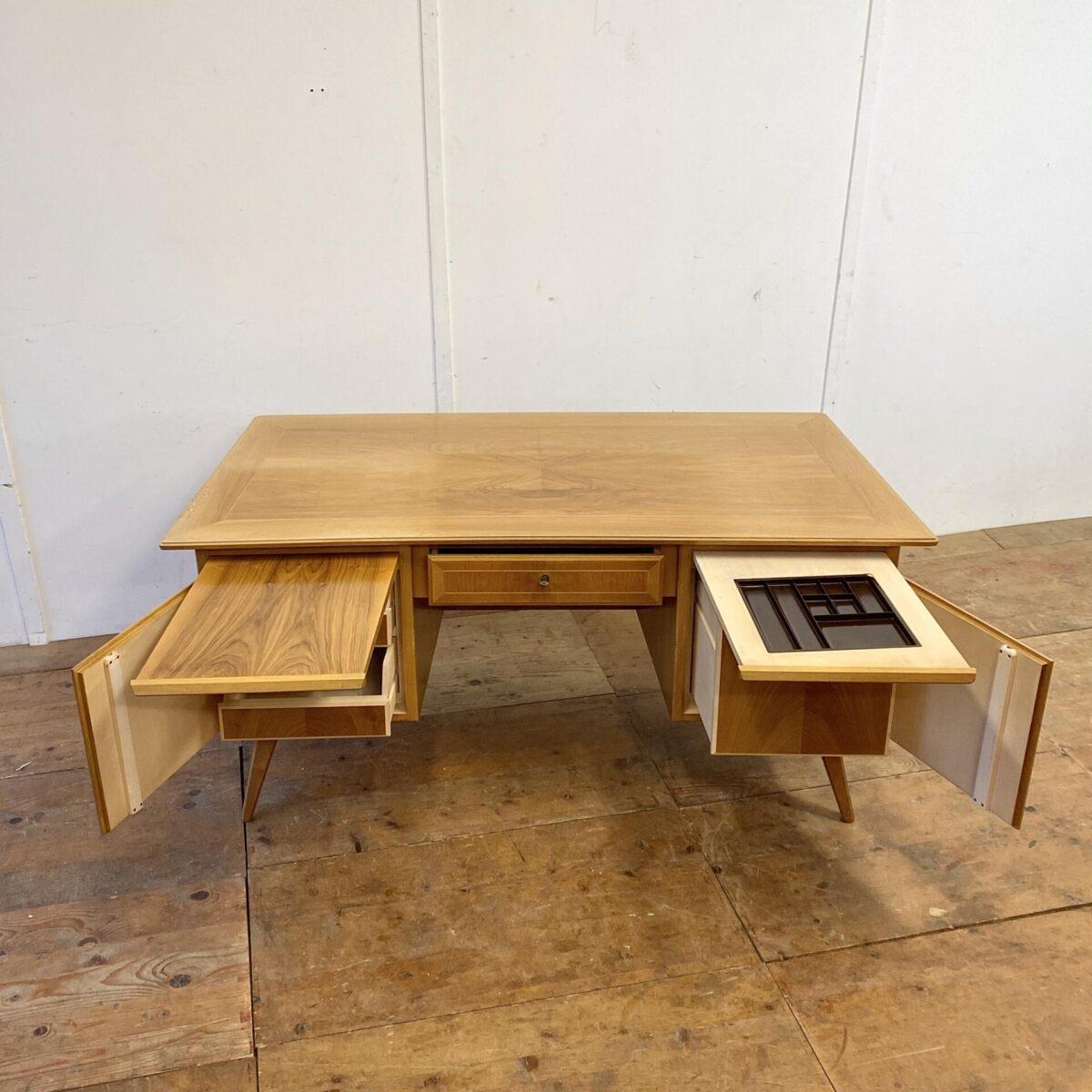 Nussbaum Schreibtisch mit Schublade. 16x80cm Höhe 74.5cm. Dieser Tisch hat eine trapezförmige Grundform, und ist leicht geschwungen. Hinter den Türen befinden sich Schubladen. Die Rückseite hat Füllungen und ein kleines Tablar.