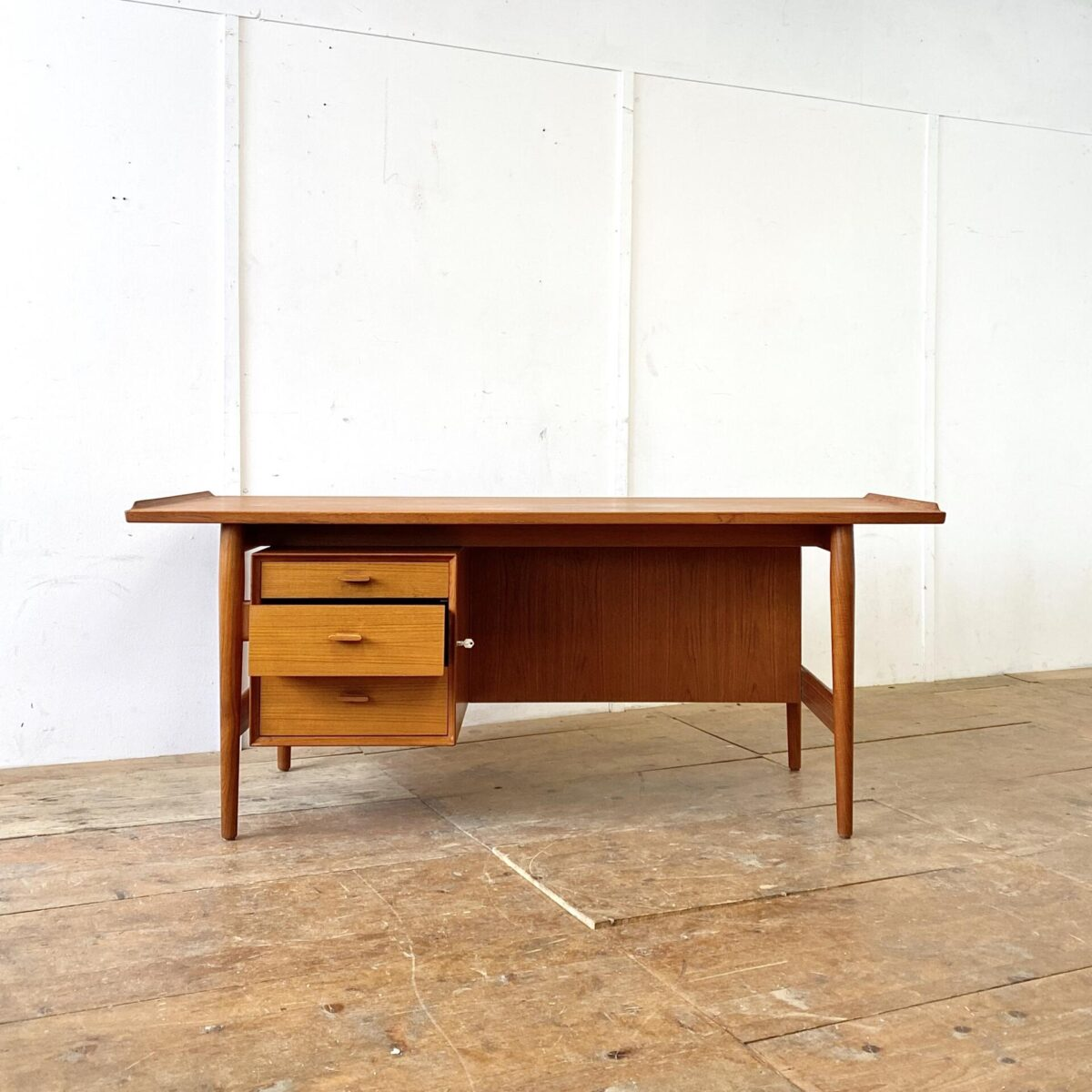 Deuxieme.shop Midcentury Teak Schreibtisch von Arne Vodder für Sibast. 178x79.5cm Höhe 72.5cm. Der Schreibtisch wurde in Dänemark, in den 60er Jahren, hergestellt. Sehr hochwertig verarbeitet, das Tischblatt hat im Bereich einer Schreibunterlage ein leichter Farbunterschied. Ansonsten alles in sehr gepflegtem Original Zustand. Der Schubladenkorpus ist abschliessbar, Schubladengriffe mit Chromstahl Details.