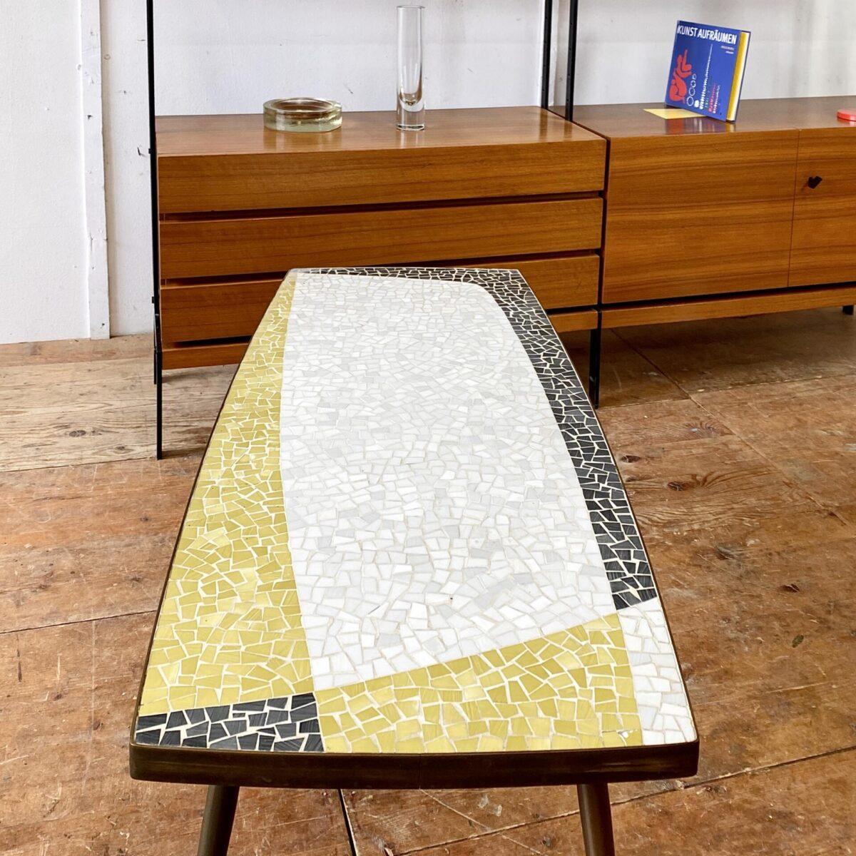 Deuxieme.shop midcentury Mosaik Salontisch mit Messing Füssen aus den 50er Jahren. 115x48cm Höhe 45cm. Das drei farbige Mosaik Tischblatt ist mit einer Messing Kante eingefasst. Die Grundform ist leicht Geschwungen. Konische Runde Messing Tischbeine, mit Standfüssen, aus einem Guss.