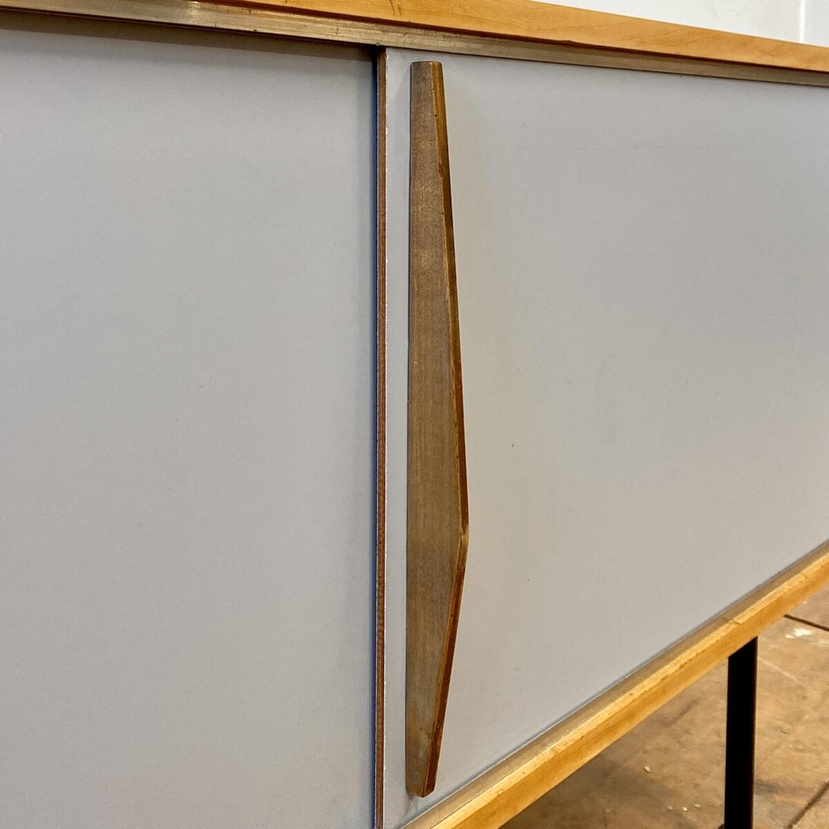 Deuxieme.shop midcentury Schlichtes Ahorn Sideboard mit Schiebetüren. 113x45cm Höhe 64cm. Die Holzelemente sind geschliffen und Natur geölt. Die Schiebetüren sind mit Kunstharz (Kelko) beschichtet. Hellgrau leicht bläulich mit drei filigranen Holzgriffen. Die Kommode steht auf schwarzen Metallfüssen mit Kunststoff Füssen.
