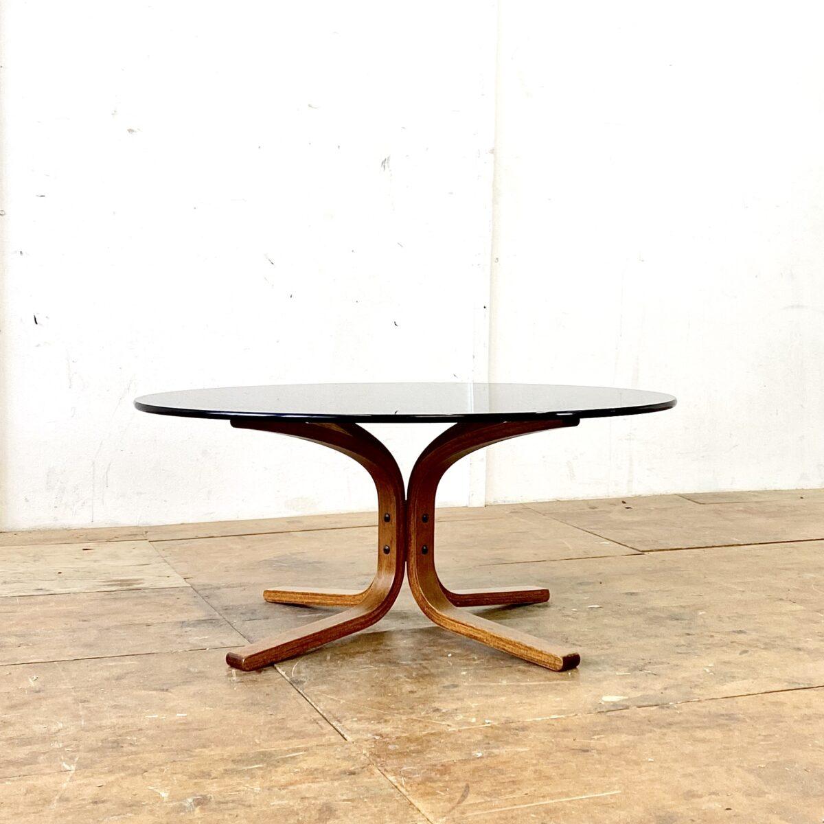 Deuxieme.shop skandinavien Glas Salontisch von Ingmar Relling für Westnofa aus den 60er Jahren. Durchmesser 90cm Höhe 40cm. Das Tischblatt aus schwarzem Rauchglas ist 12mm dick. Der Unterbau ist aus Buche Formsperrholz.