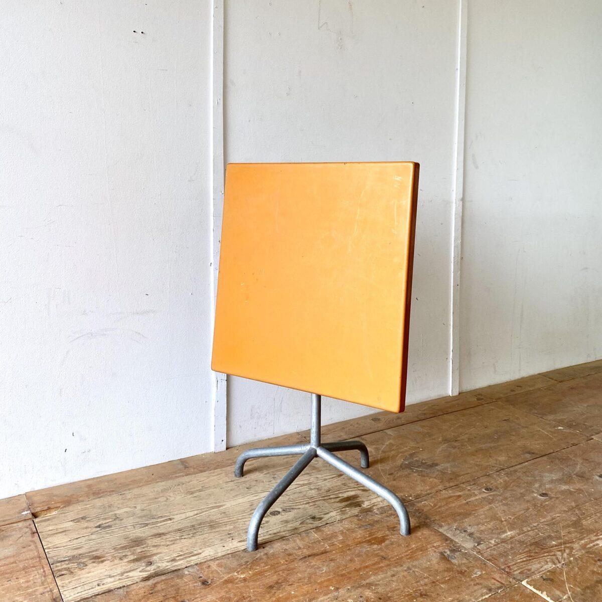 Vintage Gartentisch von Bättig. 70x70cm Höhe 70cm. Preis pro Tisch. Wetterbeständiger Klapptisch mit Fieberglas Tischplatte. Der Metallfuss ist feuerverzinkt. Die Orange Farbe ist etwas Sonnenverbleicht, ebenfalls hat es kleinere hicke und Schrammen. Polyester ist aber ein sehr langlebiges Material welches auch gut frisch lackiert oder in der gewünschten Farbe angemalt werden kann.
