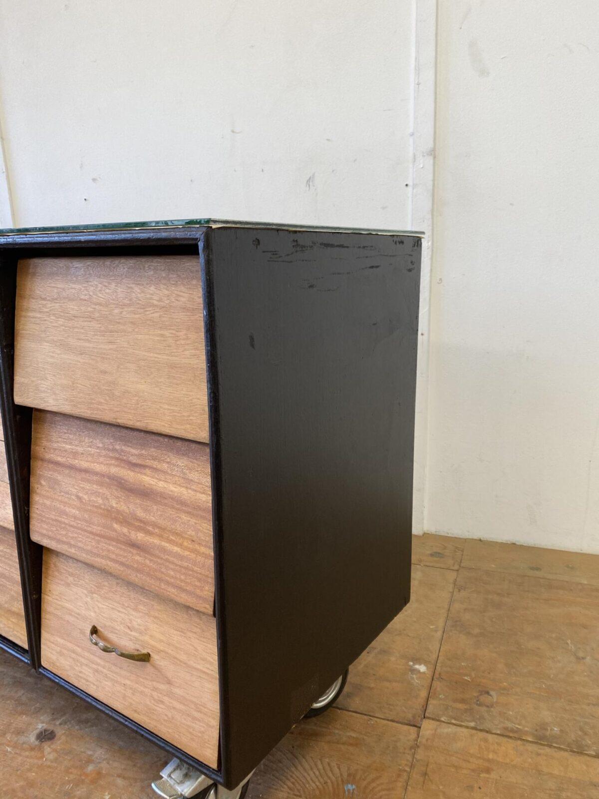 Deuxieme.shop Industrial Sideboard Schubladenkorpus. Schubladenmöbel auf Rollen mit aufgelegter Glasplatte. 180x46.5cm Höhe 77cm. Schubladenfronten aus Teak Vollholz, Möbelseiten schwarz lackiert. Die Glasplatte ist mit alten Zeitungsausschnitten unterlegt, und kann nach eigenem Gusto gestaltet werden, von Postkarten bis Leder ist vieles möglich. Passend zur Werkstatt Industrie Ausstrahlung kommt das Möbel auch mit Schrammen, Altersspuren und Patina daher. Die zwei kurzen Glasseiten wurden nicht maschinell geschnitten, sie sind jedoch nicht scharfkantig. Die Rollen laufen gut und zwei davon können blockiert werden.