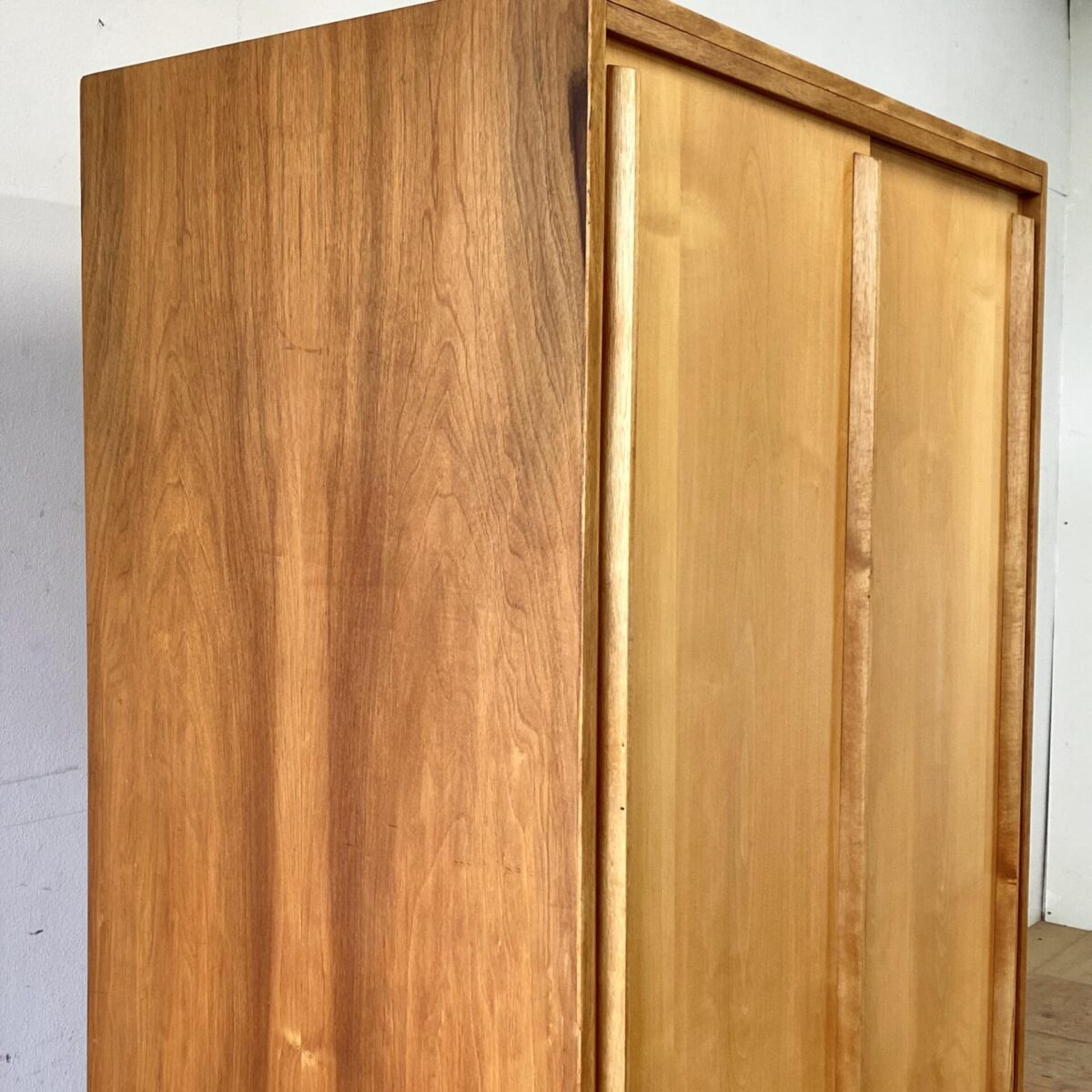 Deuxieme.shop midcentury pavatex Schrank Swiss Design. Kleiderschrank mit Schiebetüren aus den 50er/60er Jahren. 166x100cm tiefe 55cm. Der Schrank ist komplett überarbeitet, Holzoberflächen mit Naturöl behandelt. Aussen Nussbaum furniert, Schiebetüren aus Ahornholz. Innen ein Tablar mit Kleiderstange, weitere Tablare sind nach Absprache möglich.