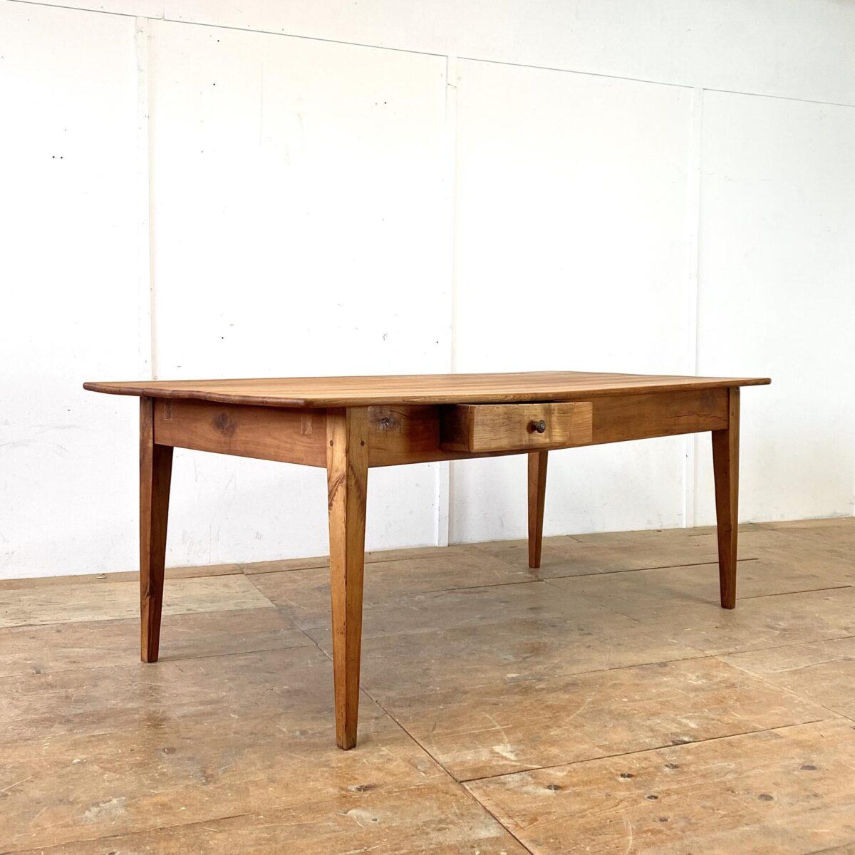 Deuxieme.shop antiker Kirschbaum Tisch. Alter Kirschbaum Biedermeier Tisch mit Schublade. 201x93cm Höhe 76cm. Der Tisch hat ein paar Flicke im Unterbau, und auf einer Stirnseite einen Riss, Tischblatt und Beine leicht verzogen. Aber alles in stabilem funktionalen Zustand. Das rötliche Kirschbaum Holz, mit Alterspatina, ist geschliffen und mit Naturöl behandelt. An diesem Holztisch finden angenehm 8 Personen Platz. Die grosszügige Tiefe von 93cm ist eher selten bei solchen Tischen aus der Zeit.