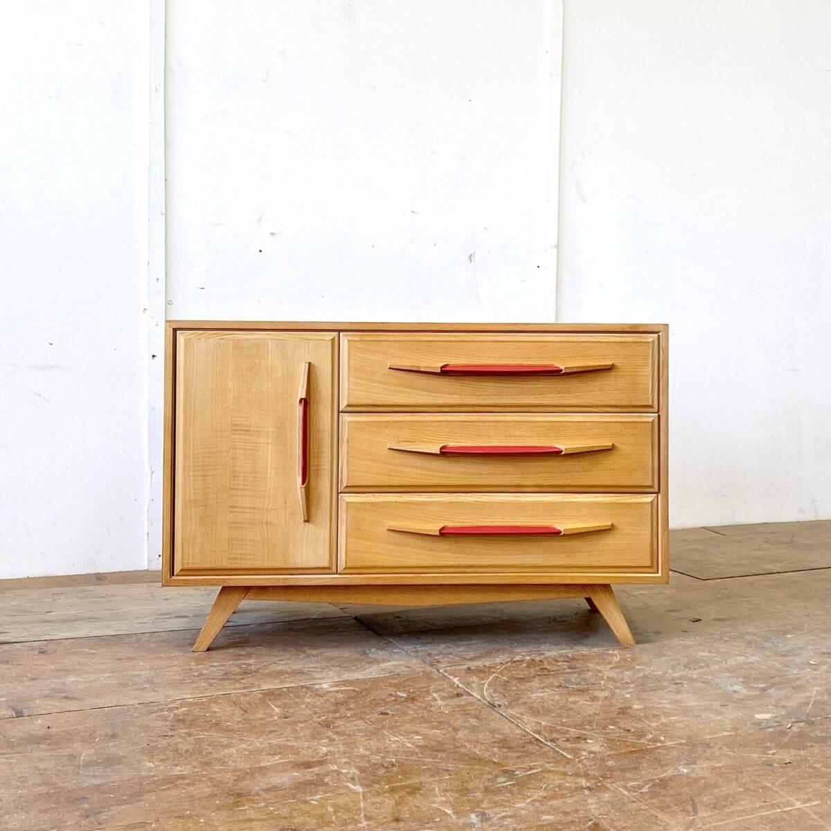 Deuxieme.shop midcentury sideboard vintage Kleider Kommode. Schweizer Kommode von Corta Multiform 50er Jahre. 103x42cm Höhe 67.5cm. Das Sideboard ist aus Eschenholz, Schubladen und Türgriffe mit rotem Kunstleder. Hinter der Türe befindet sich ein Tablar.